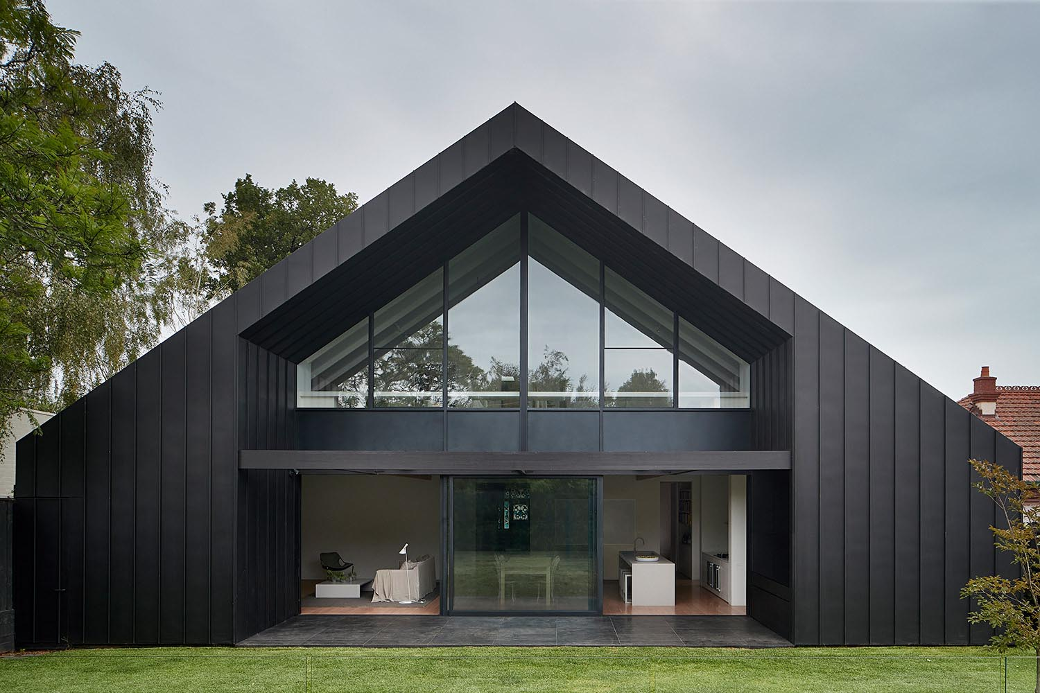 A modern black house addition that opens to the yard.