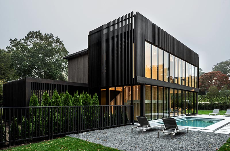 A modern two story black house with walls of windows.