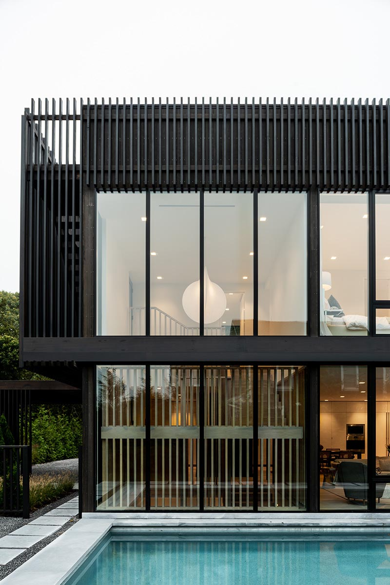 The rear of this modern home is fully glazed on both levels with custom Marvin Modern windows that create a strong connection between the home's interiors and the outdoors.