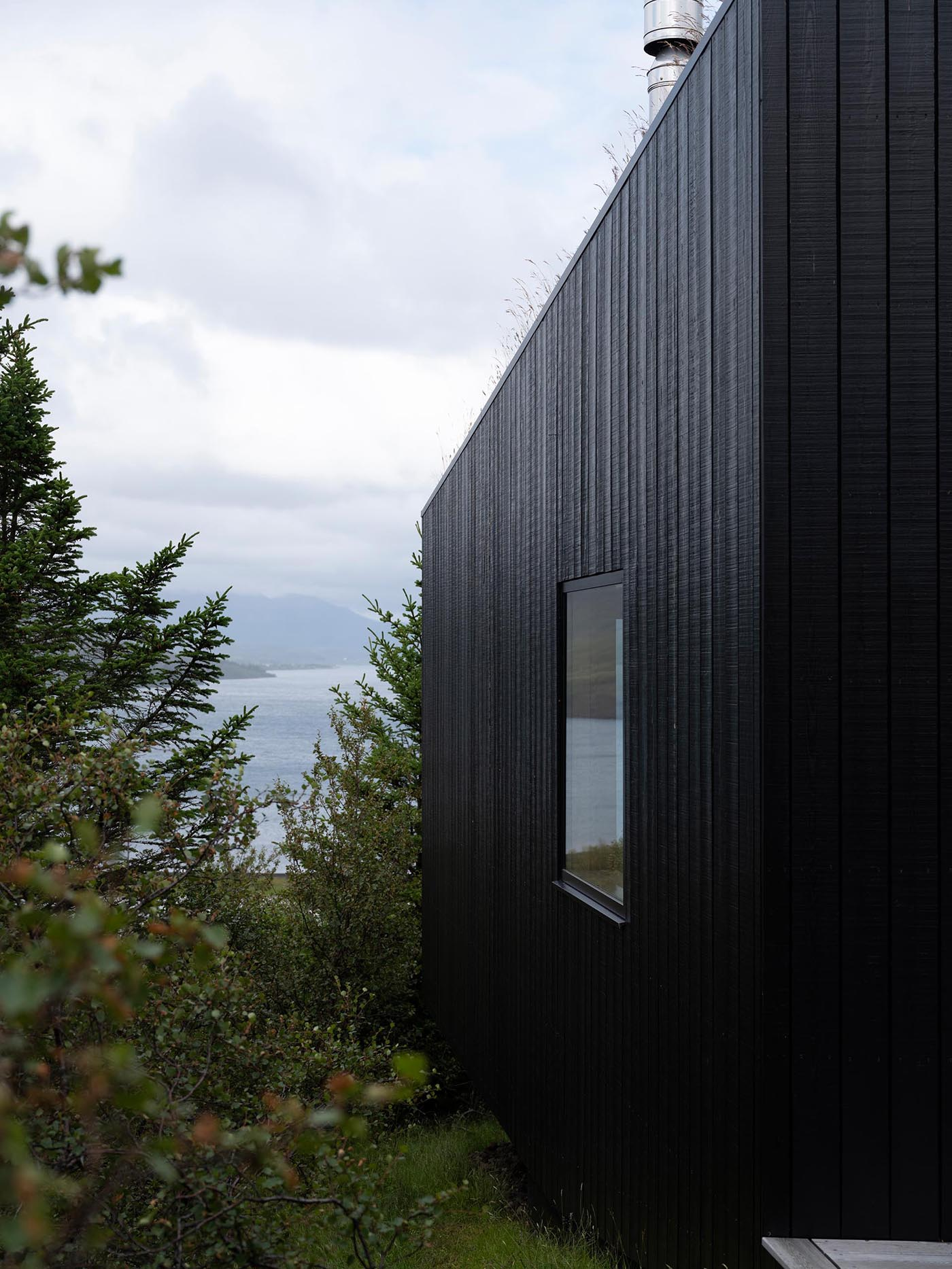 A modern home clad in blackened wood siding.
