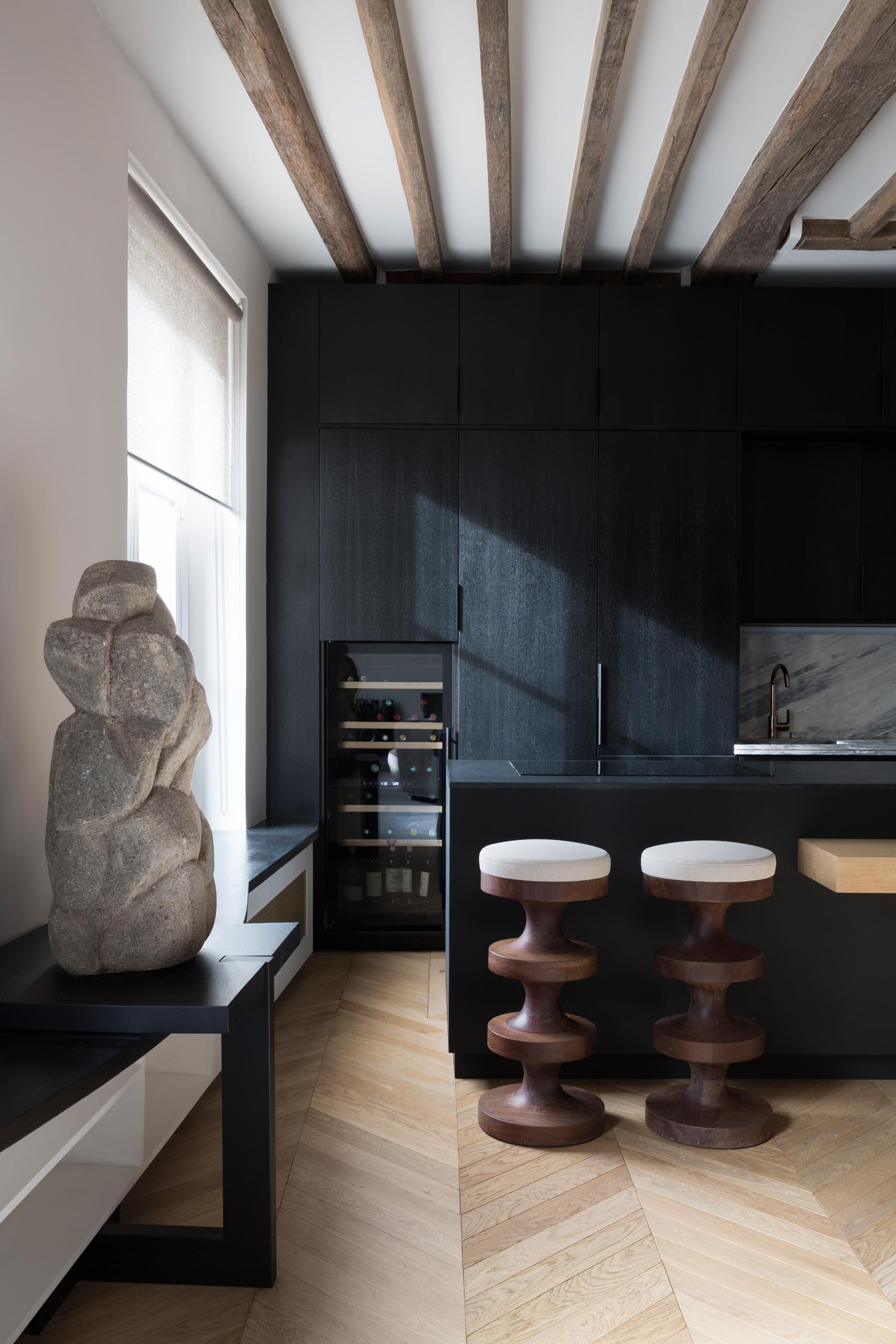 A modern matte black kitchen with a wine fridge and exposed wood beams.