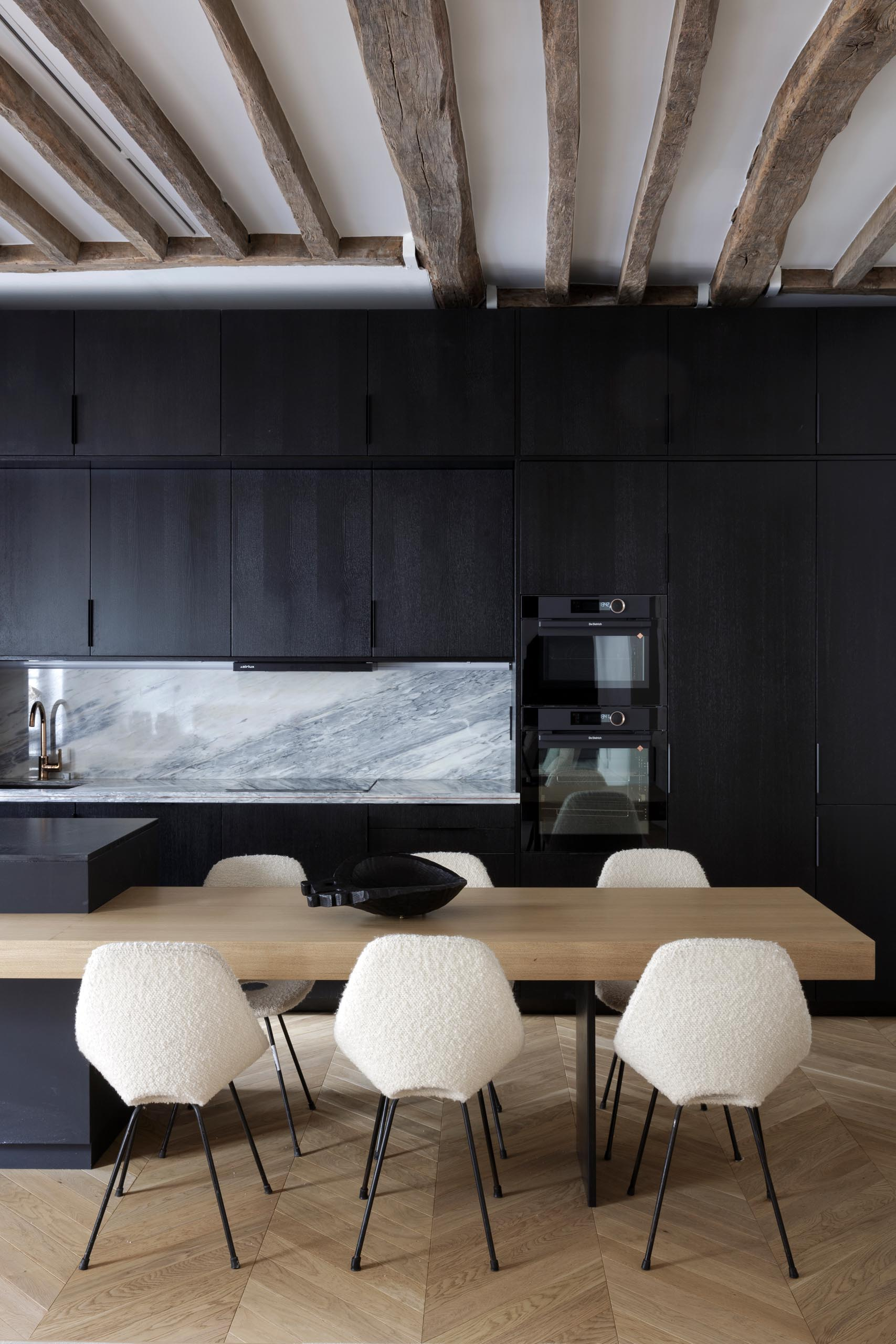 A modern matte black kitchen with a black appliances and exposed wood beams.