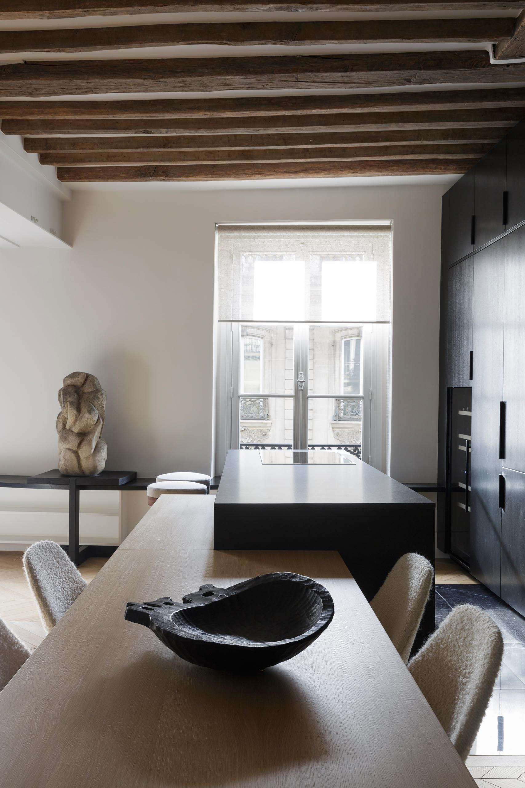 A modern matte black kitchen with a black appliances, exposed wood beams, and an island with a built-in dining table.