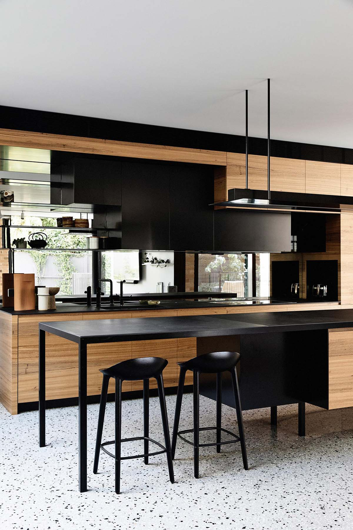 In this modern kitchen, hardware free cabinets line the wall, while the black island and shelving creates a contrasting element, and the mirrored backsplash reflects the living room.
