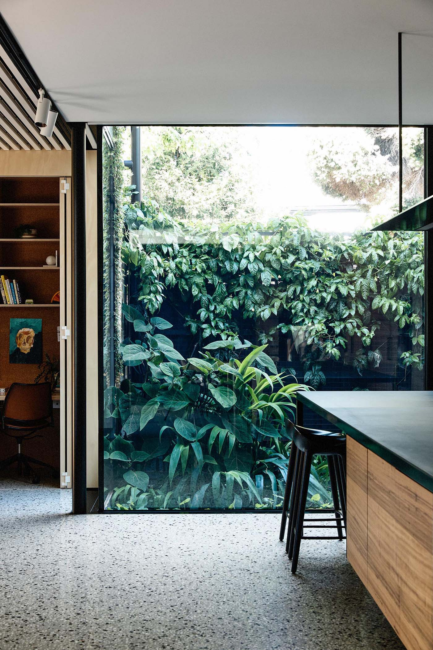 A home office tucked into a closet is adjacent to a large window that provides an unobstructed view of the garden outside.