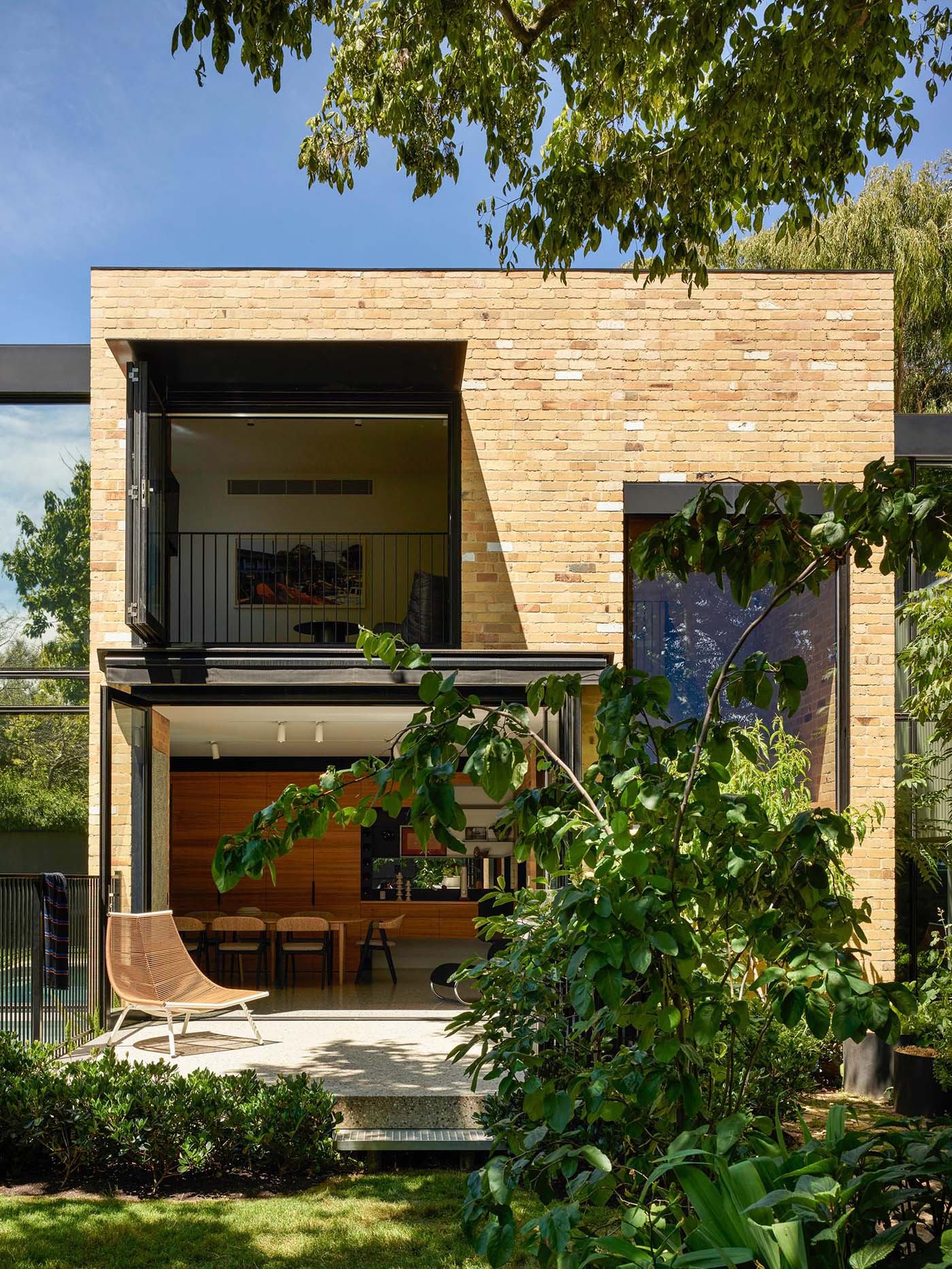 A modern home with indoor/outdoor living spaces, has been built using recycled yellow brick.