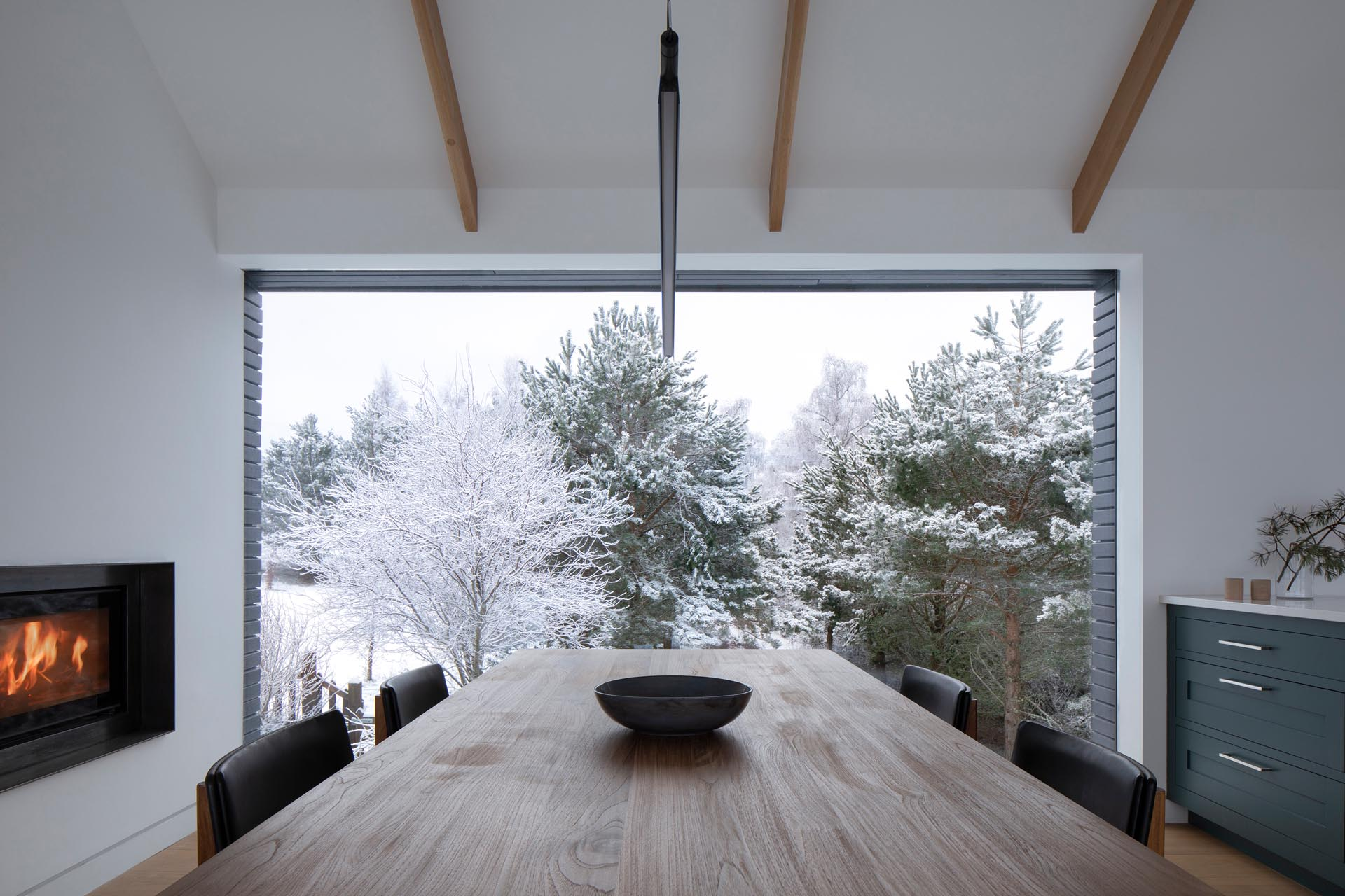 A modern dining room that enjoys a picturesque view of the trees.