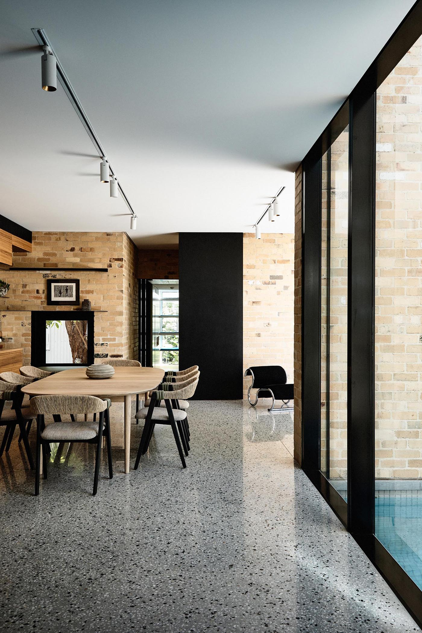 A modern dining room with brick walls and a wood table.