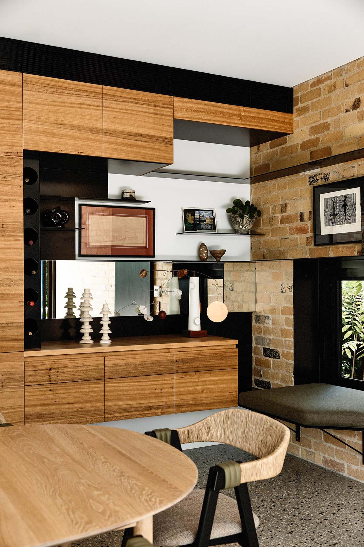 The wood cabinets from the kitchen continue through to this dining room, and result in an open niche with shelving. Beside the cabinets and in the brick wall, there's a small built-in window seat.
