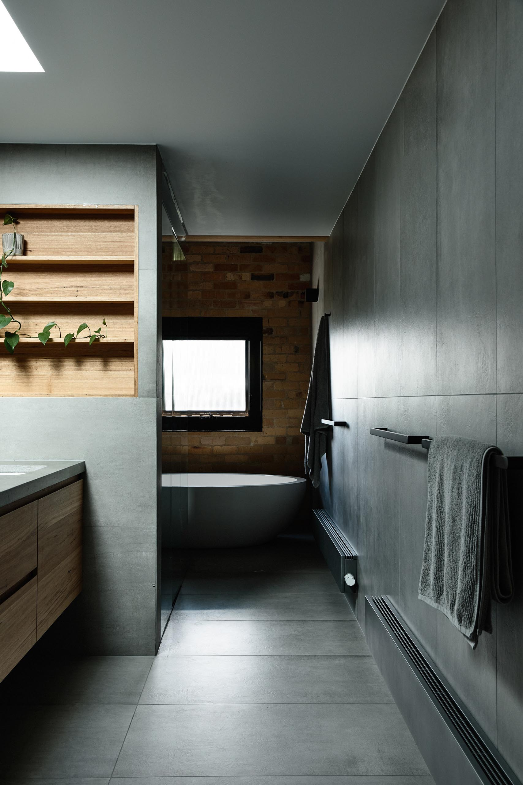 In this modern bathroom, gray walls and floors are accented by a wood-lined shelving niche, small metallic tiles, and a white freestanding bathtub.