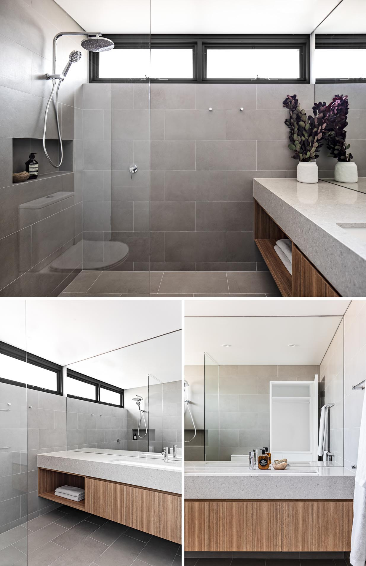 A modern bathroom with large gray tiles that cover the walls and floor, a floating wood vanity, and a shower niche.