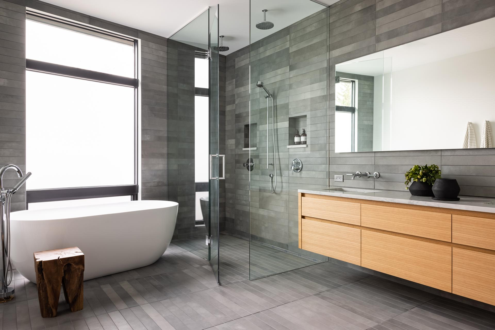 In this modern bathroom, grey tiles cover the walls and floor, while a floating wood vanity adds a natural element, and a white freestanding tub is positioned by the glass-enclosed shower.