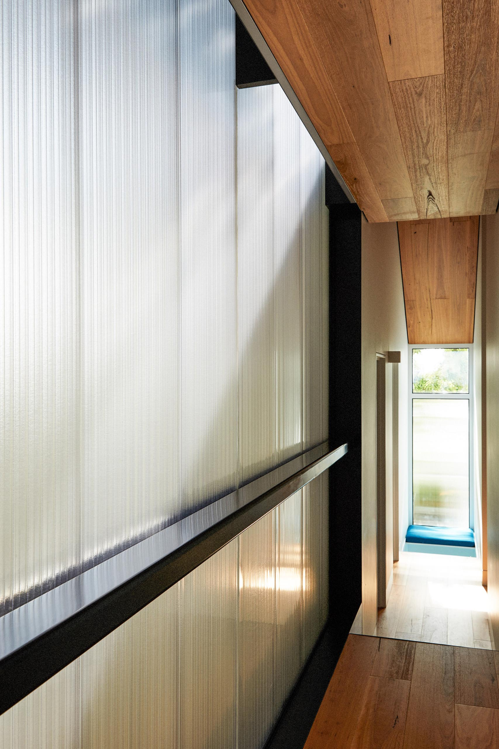 At the end of this hallway is a small seating niche by the window that includes upholstered benches, ideal for when the children want to have a quiet moment.