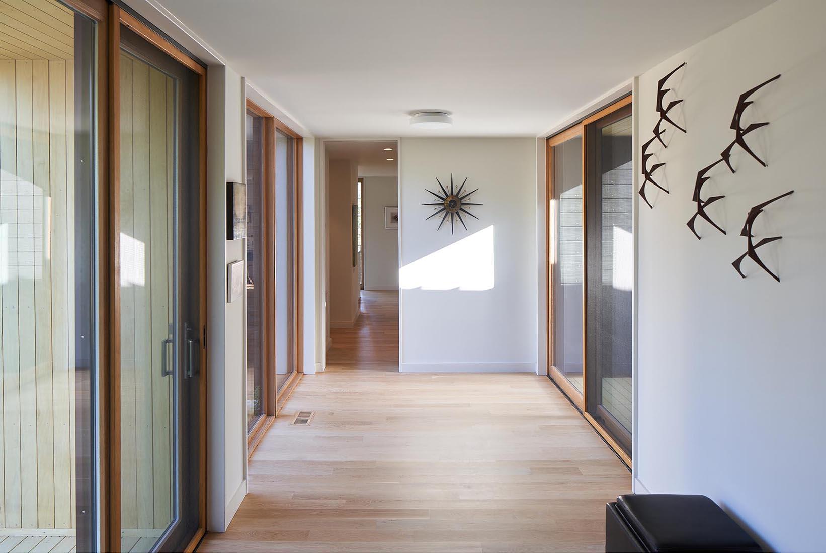 A modern hallway with light wood flooring.