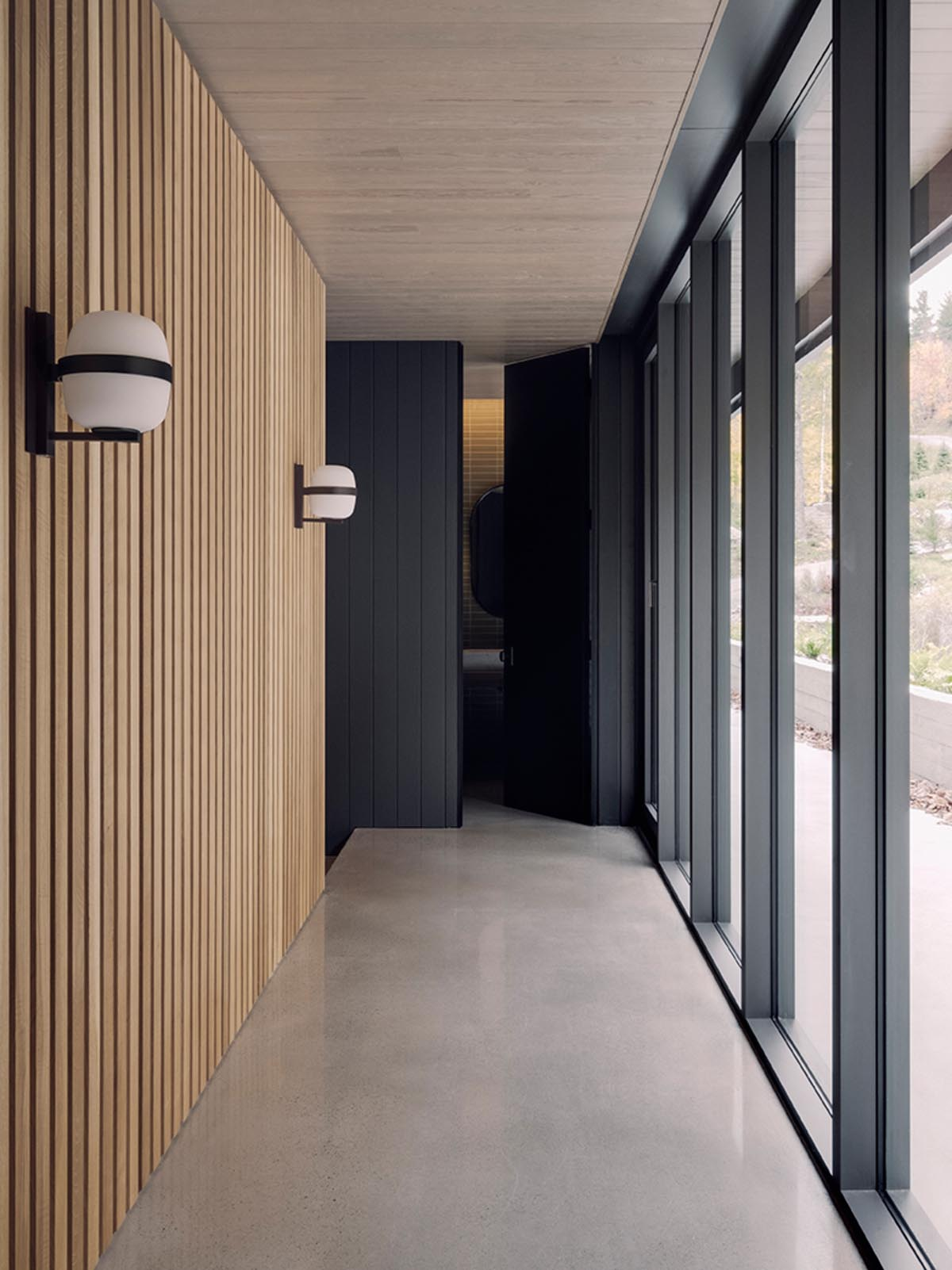 A modern hallway with a wood slat wall and floor-to-ceiling windows.