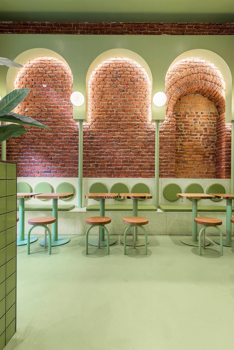 A new restaurant has brick walls and green interior design elements.