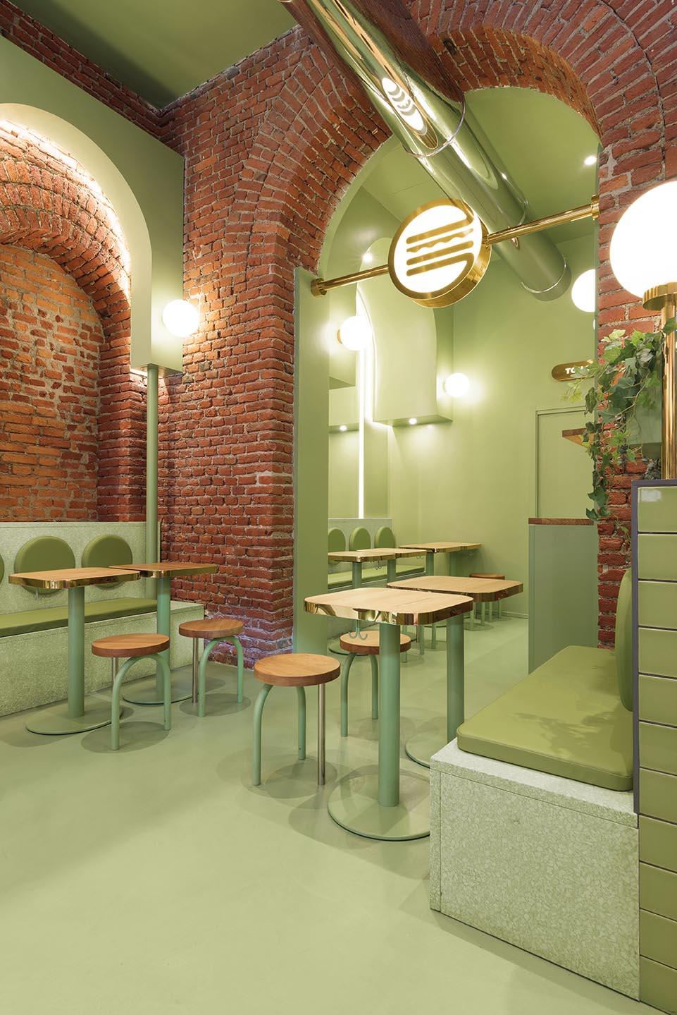 A new restaurant in Milan, Italy, uses a colorful green and brick interior to draw people inside.