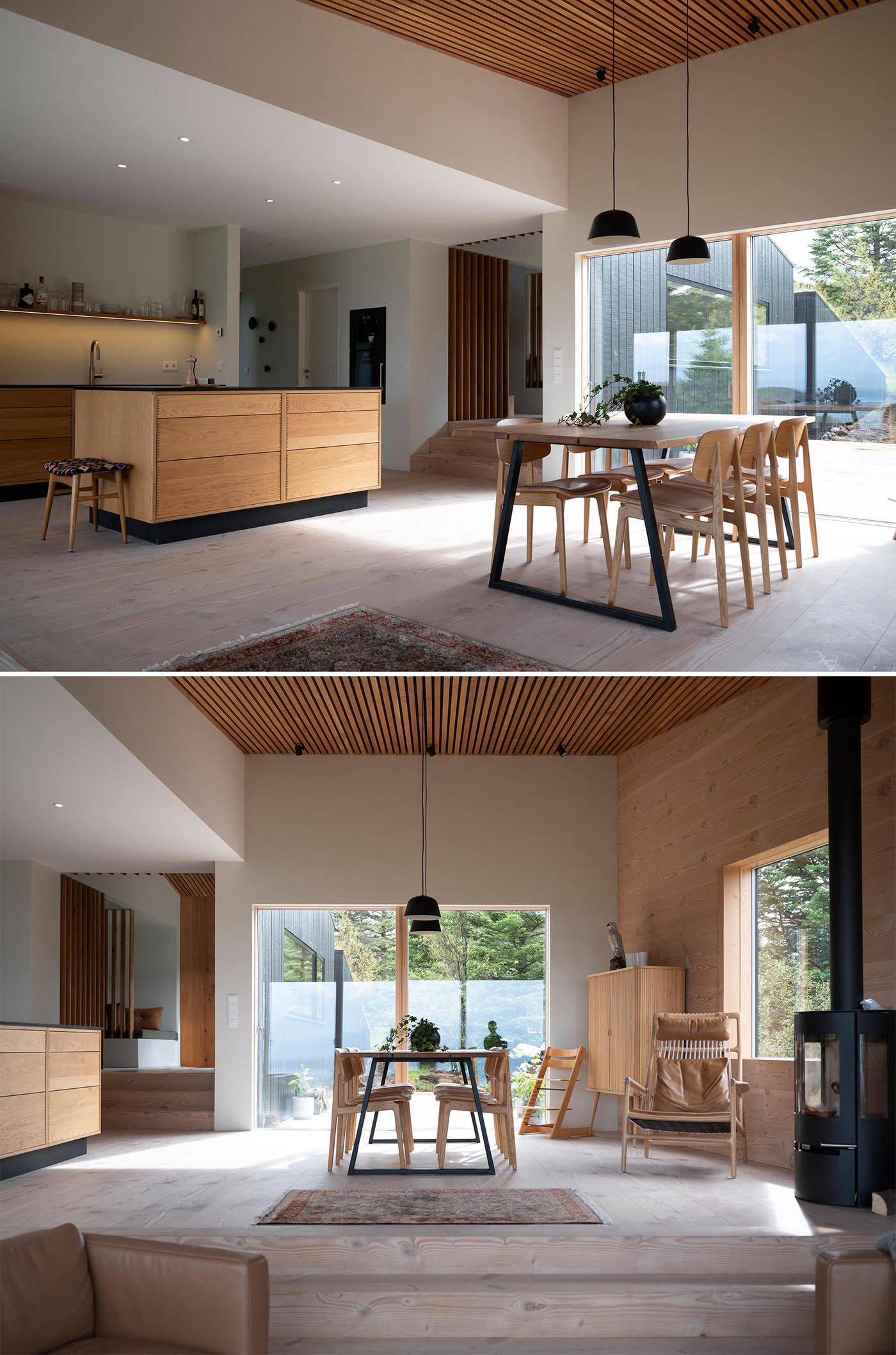 Inside this modern home, there's an open plan kitchen and dining room. Both have black accents, however the dining room also includes a wood slat ceiling and a black fireplace.