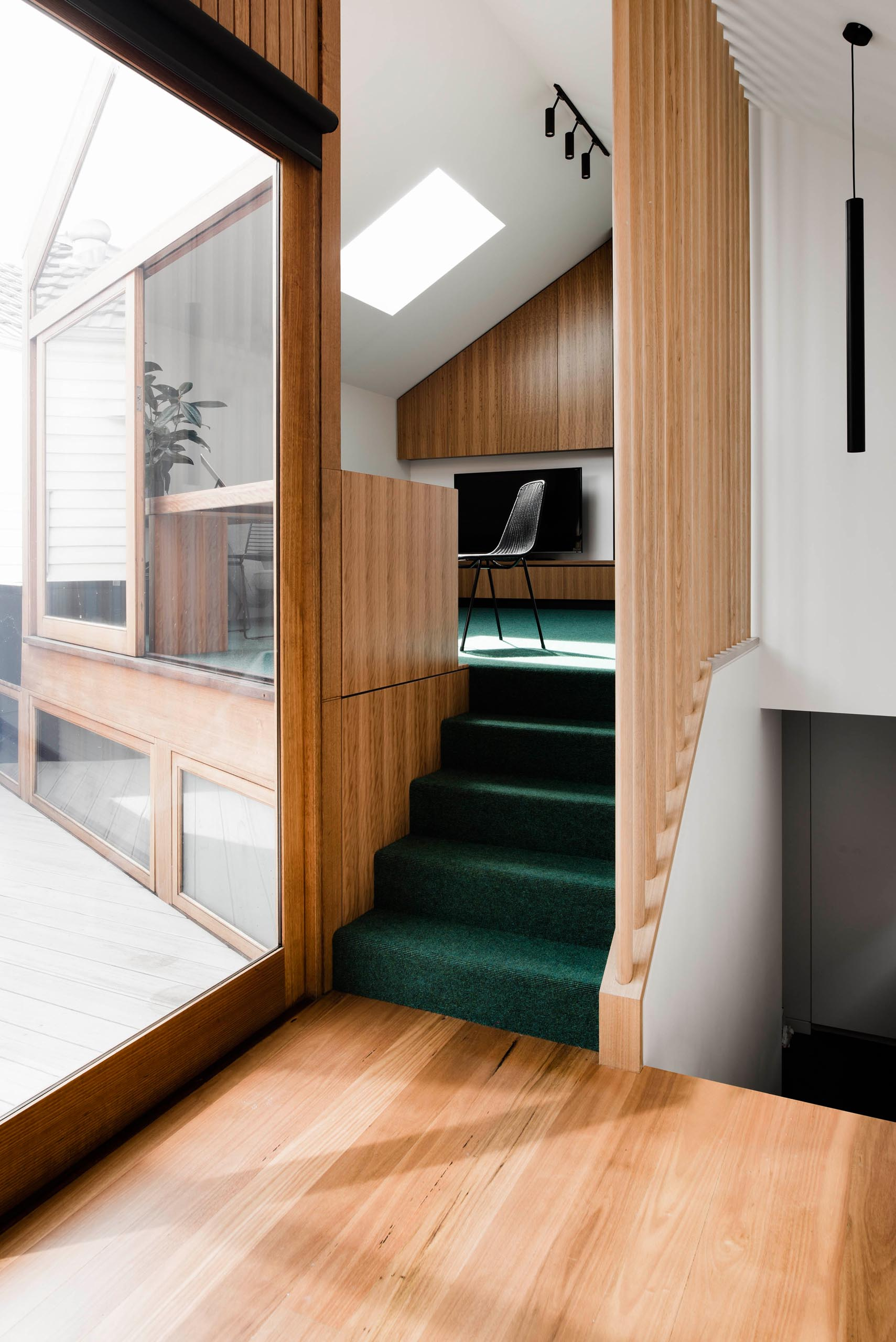 A colorful surprise is included in this modern home in the form of a deep green carpet that travels up the stairs and into the home office.