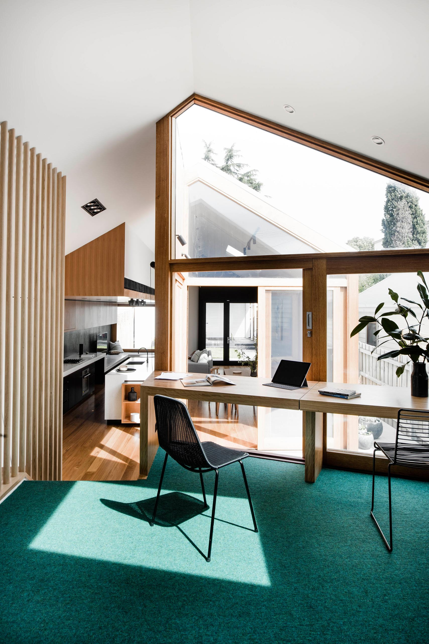 A modern house with a home office that has green carpet and a desk that lines the angled window and overlooks a small courtyard.