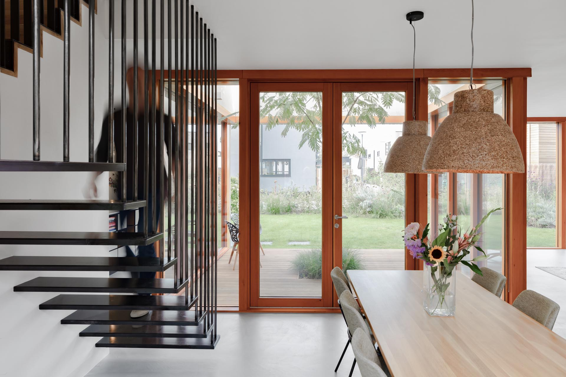 Modern black stairs that contrast the wood and glass in the dining room.