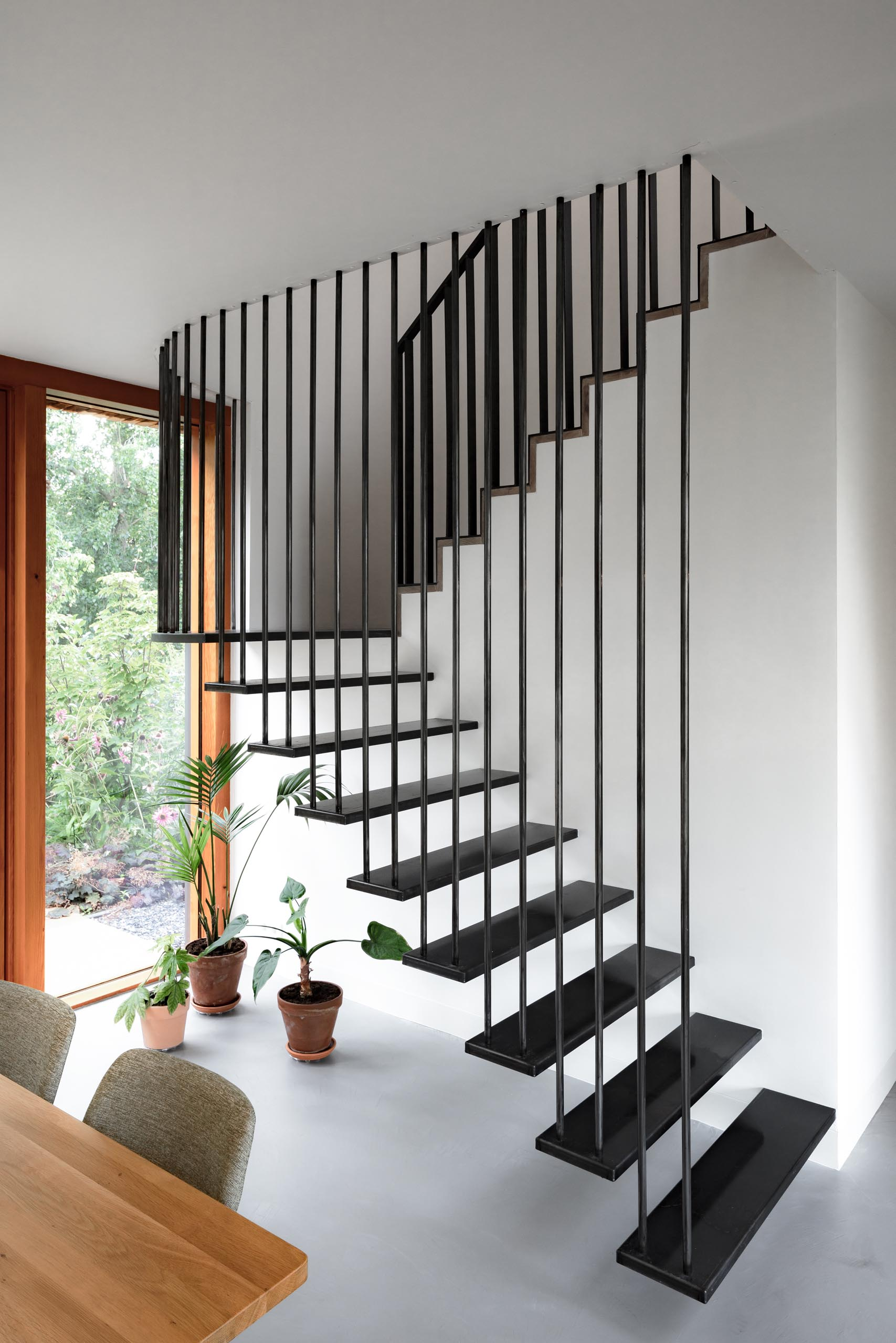Modern black stairs that contrast the white walls and wood accents.