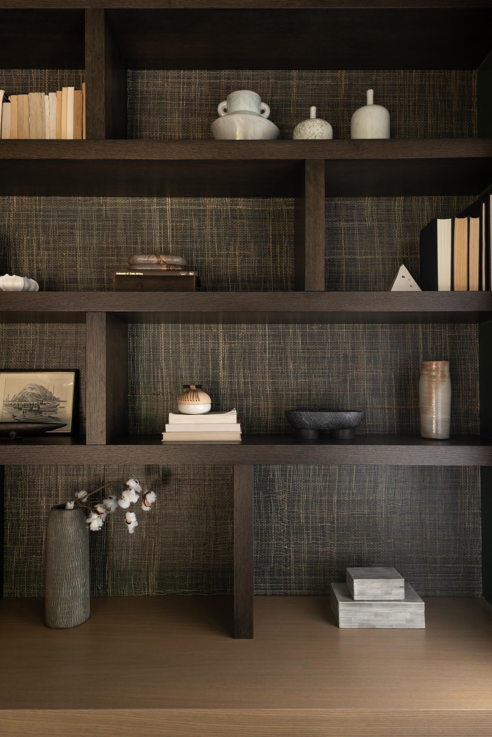 A modern and dramatic bookshelf includes a dark stain and a natural wallpaper backing.