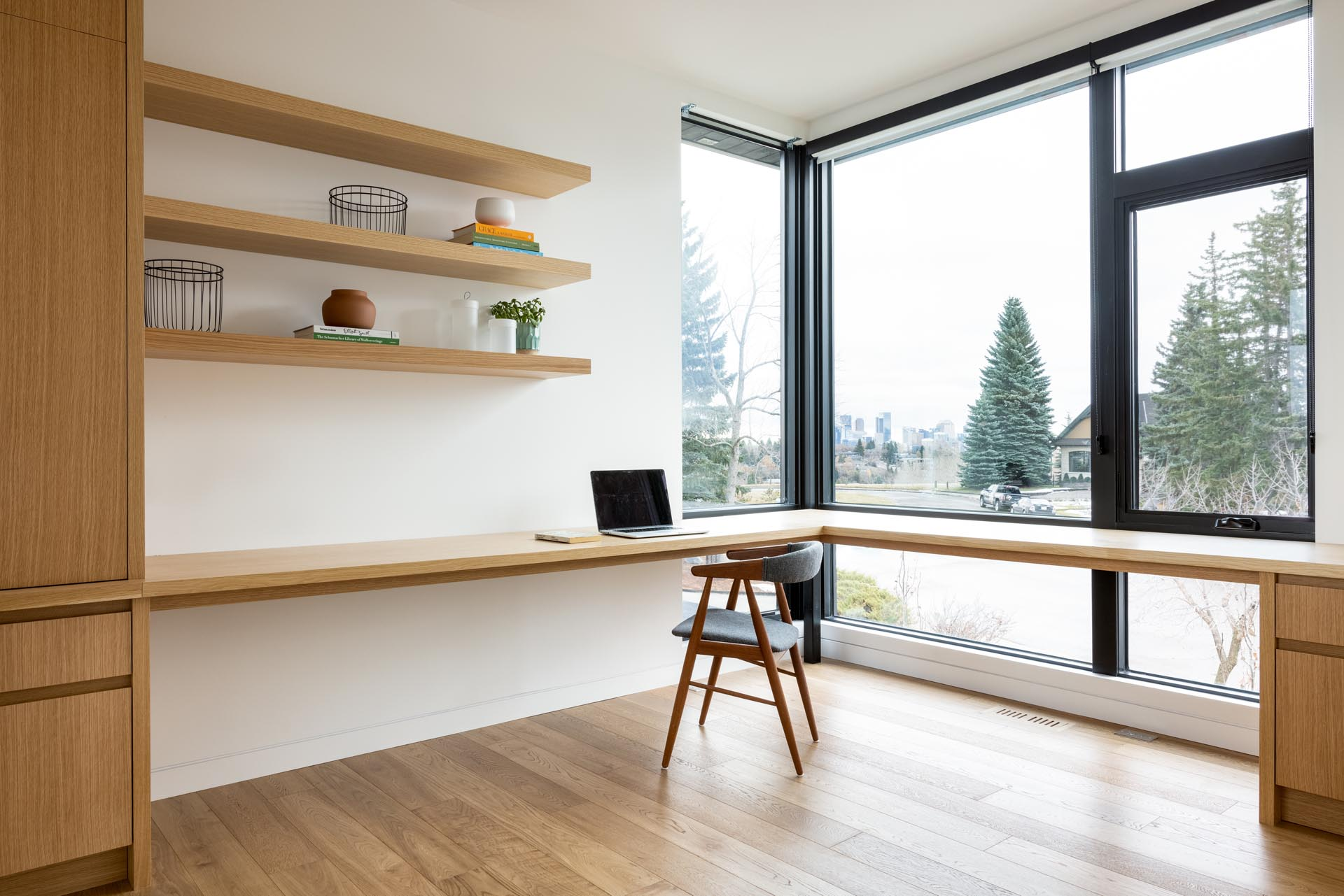 A home office with a custom designed wood desk that wraps around the corner of the room. Open shelving and cabinets add additional storage to the room.