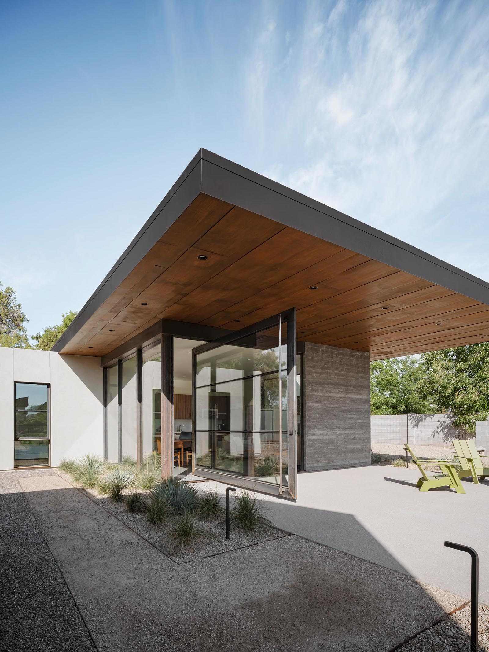 The 12 foot wide pivoting glass door of this small and modern home connects the interior spaces to the patio.