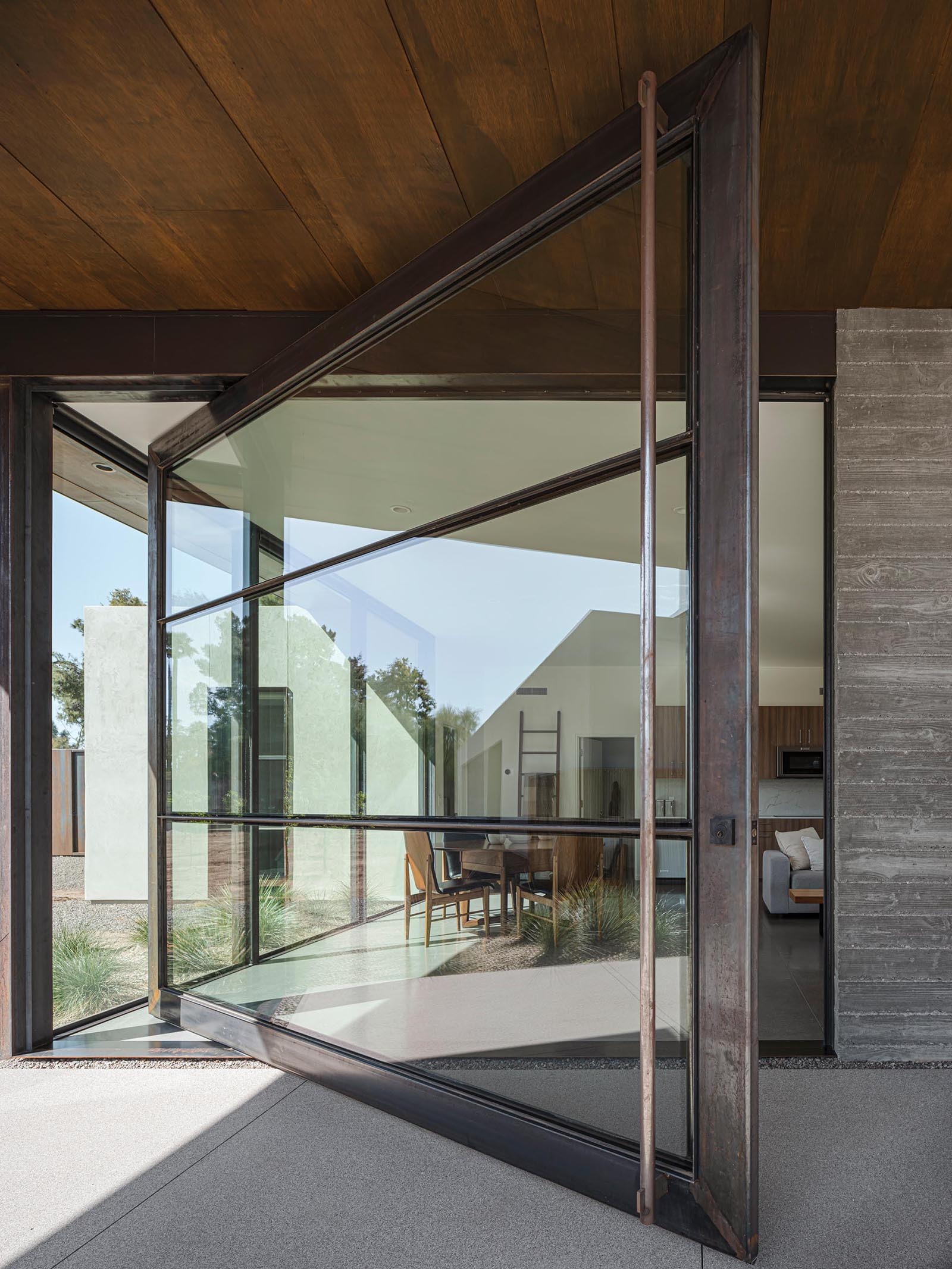 A modern oversized pivoting glass door with a metal frame.