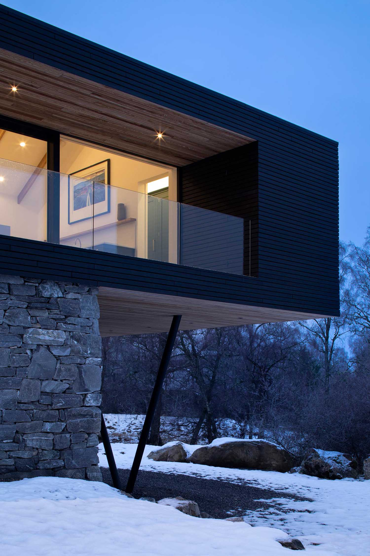 A modern home addition with a material palette of local natural stone, Siberian Larch, natural slate, blackened stainless steel, and glass.