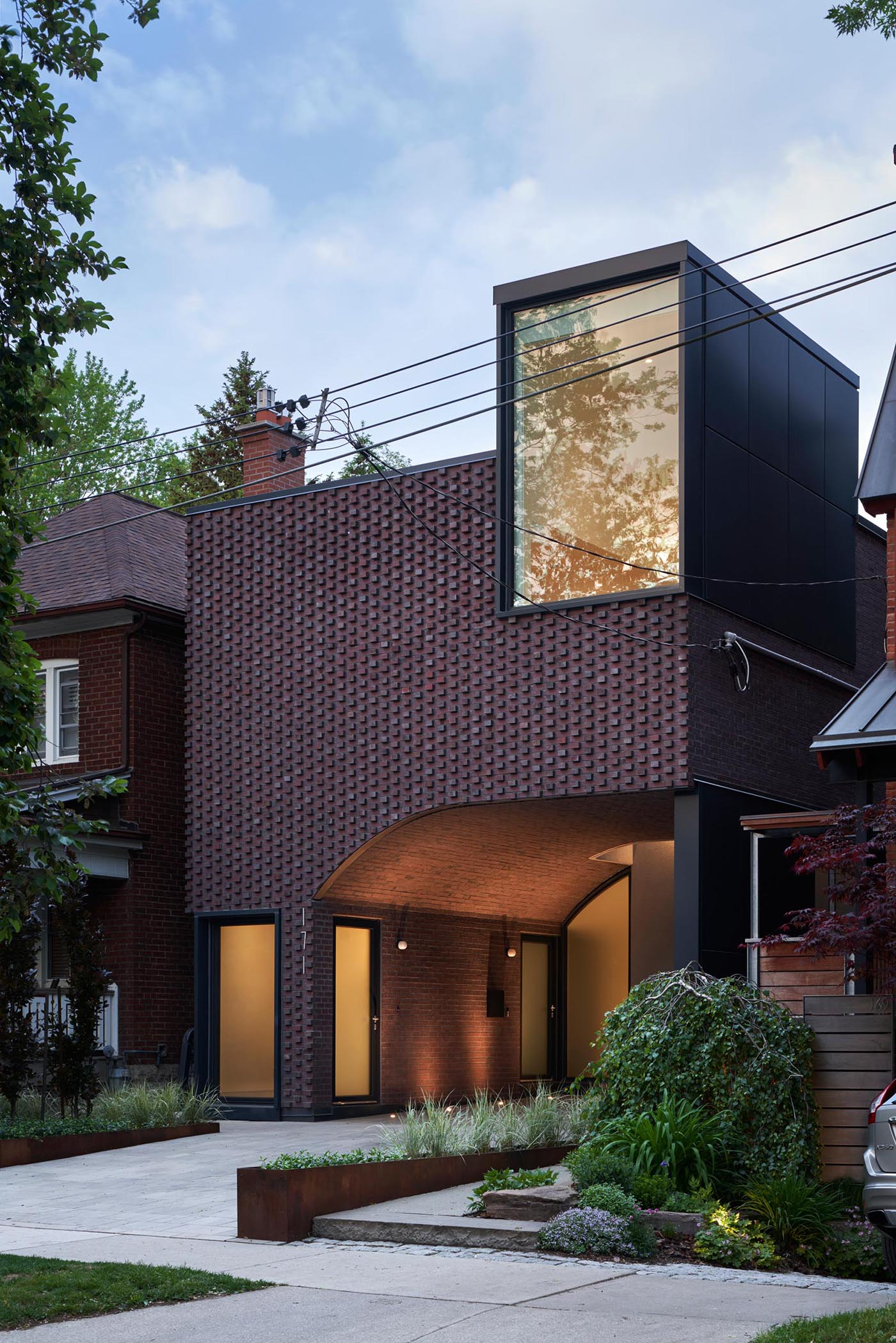 At dusk, the lights from the interior of the home and the featured exterior lighting highlight the windows and doors, and create a soft ambient glow.