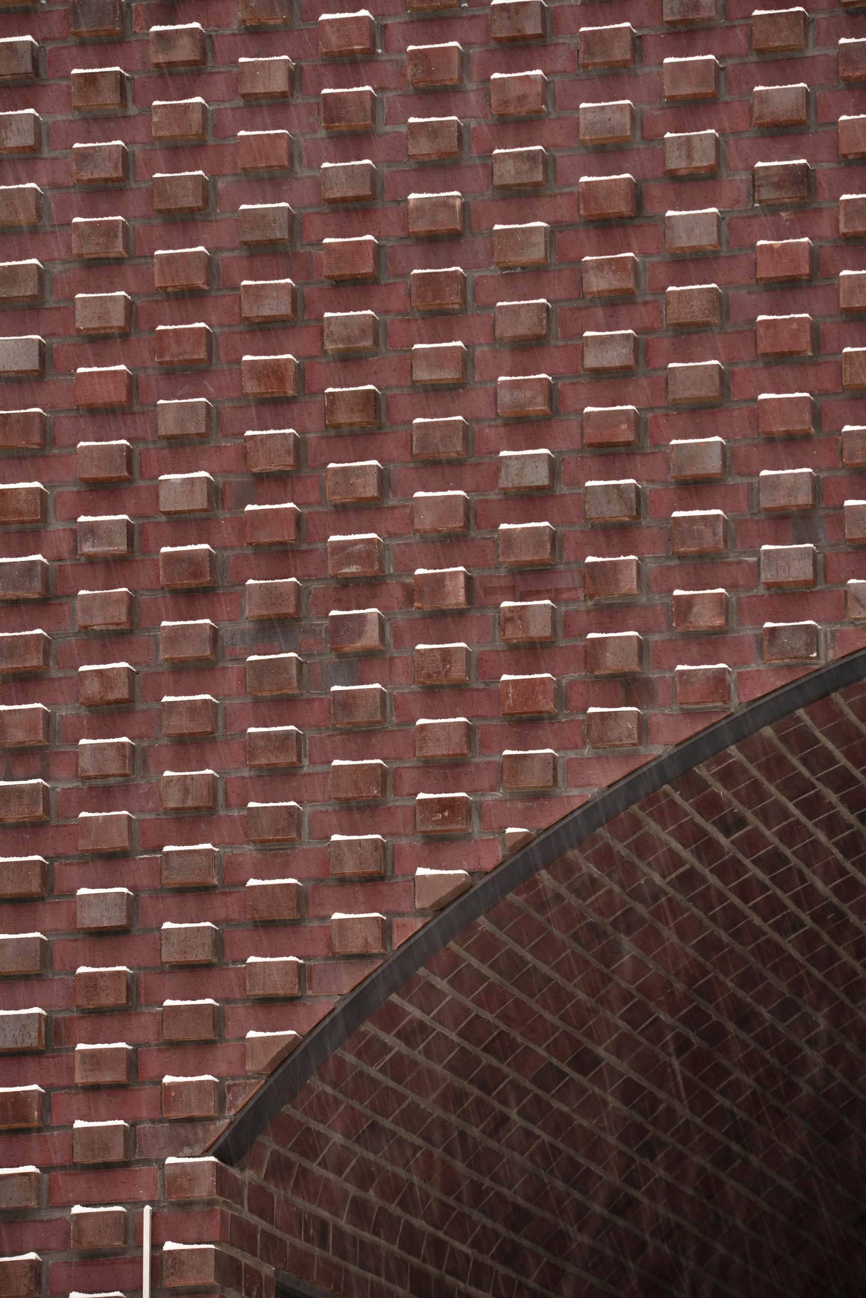 In the summer, the brick protrusions texture the facade with stark shadows, and in the winter the texture transforms through bricks creating shelves for the snow to fall on.