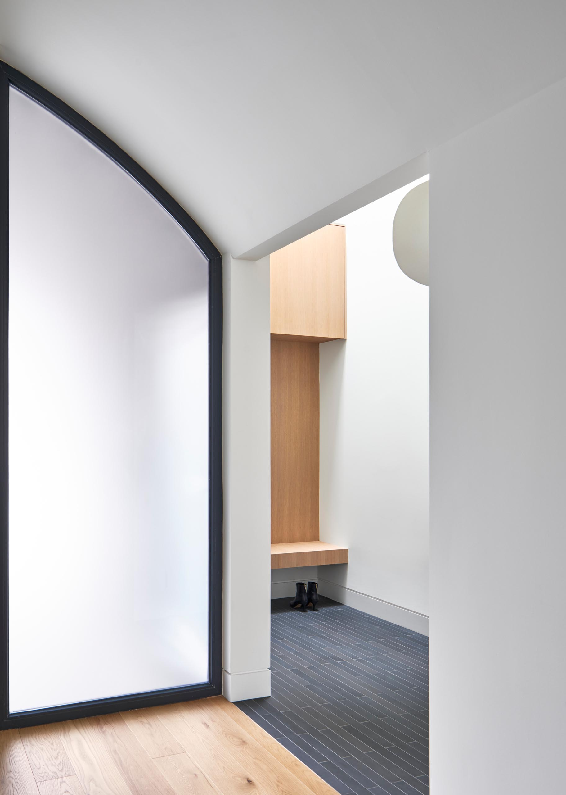 Inside this modern home, there's a small entryway with a bench for taking off shoes and coats.