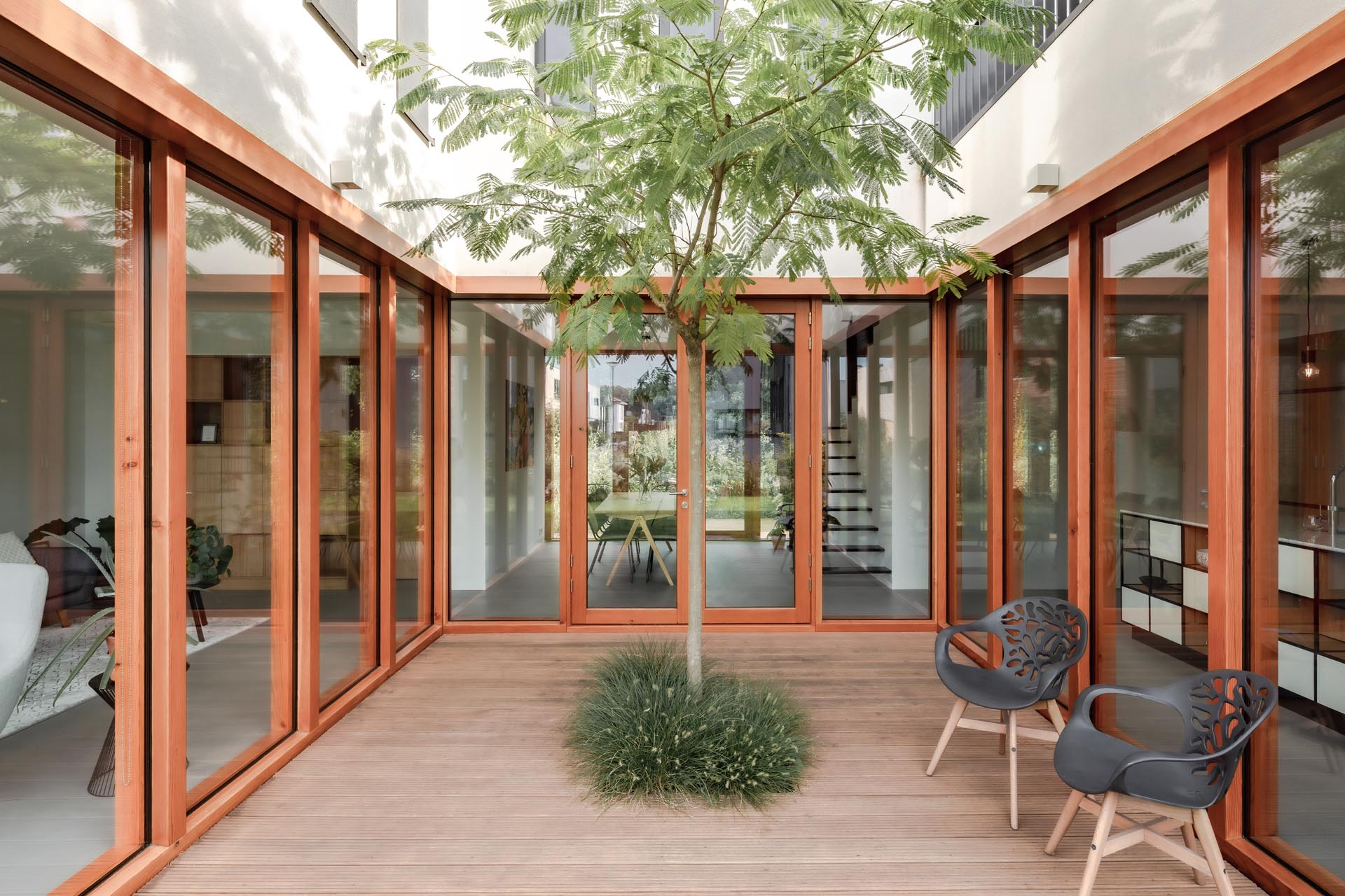 A modern home with windows and glass doors that wrap around a courtyard with a tall tree and wood deck.