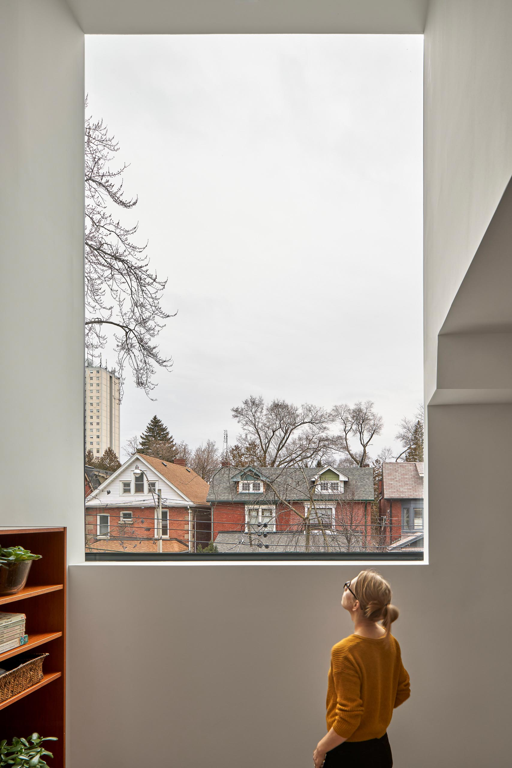 On the upper floor of this modern home, there's a large window that frames the neighborhood.