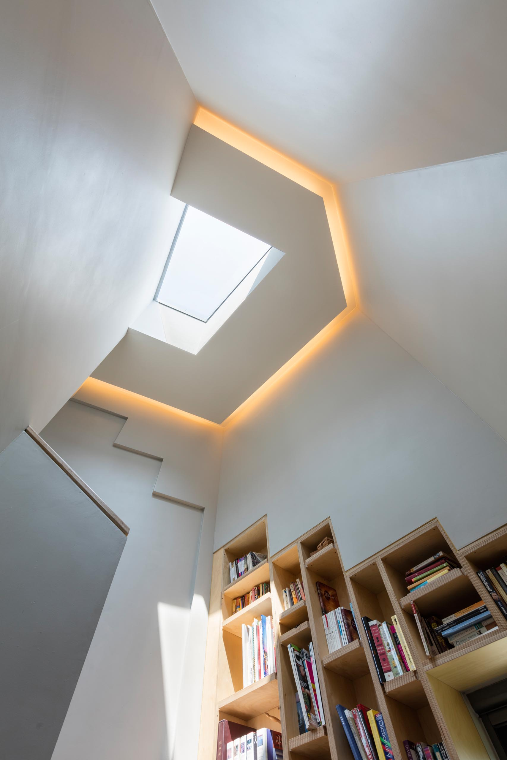 A modern home with a skylight, hidden lighting, and built-in bookshelves.