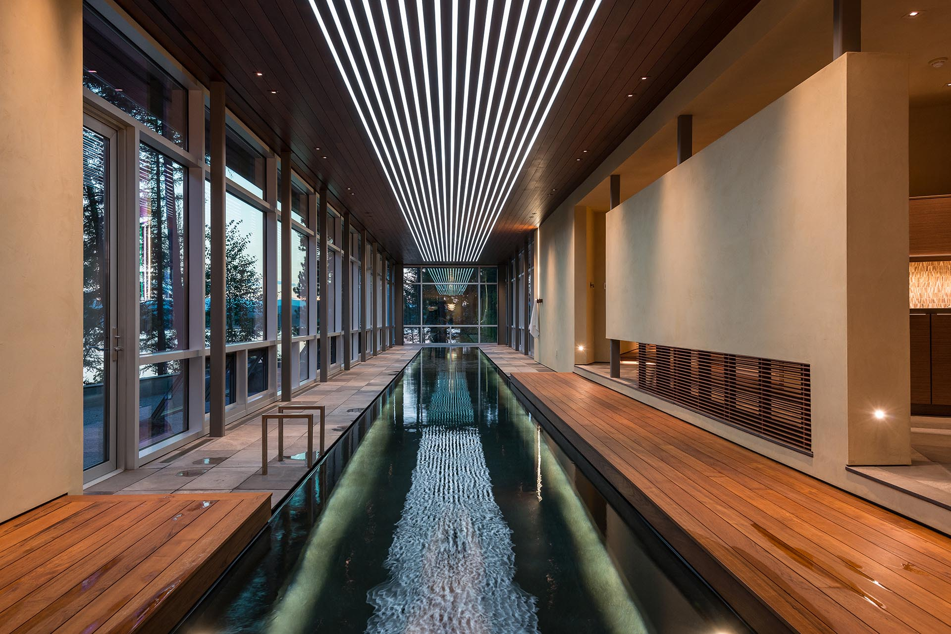 An indoor swimming pool with lighting integrated into the ceiling.