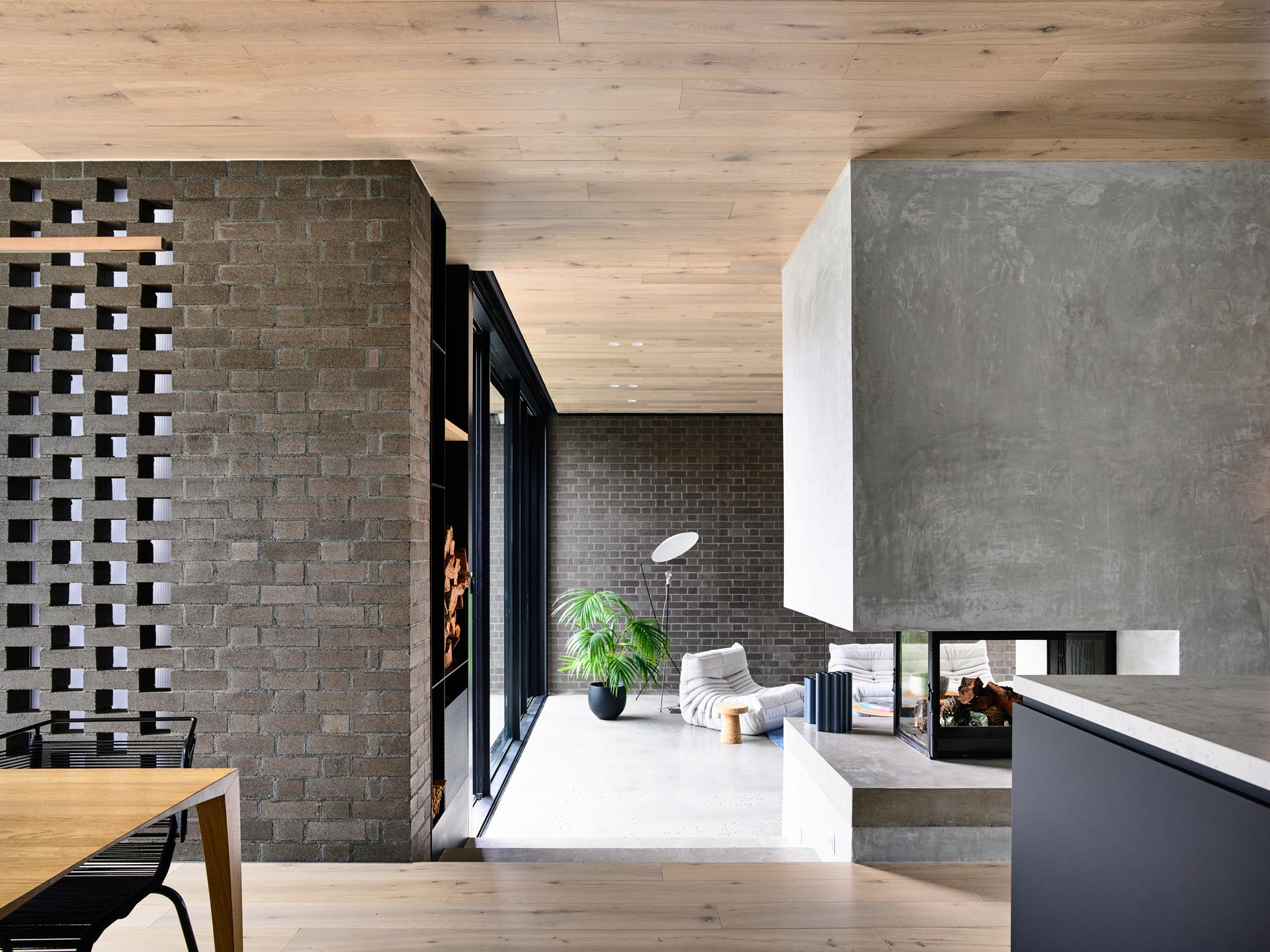 This modern interior showcases dark brick walls, as well as a wood ceiling, and a see-through fireplace that can be enjoyed from both the kitchen and the living room.