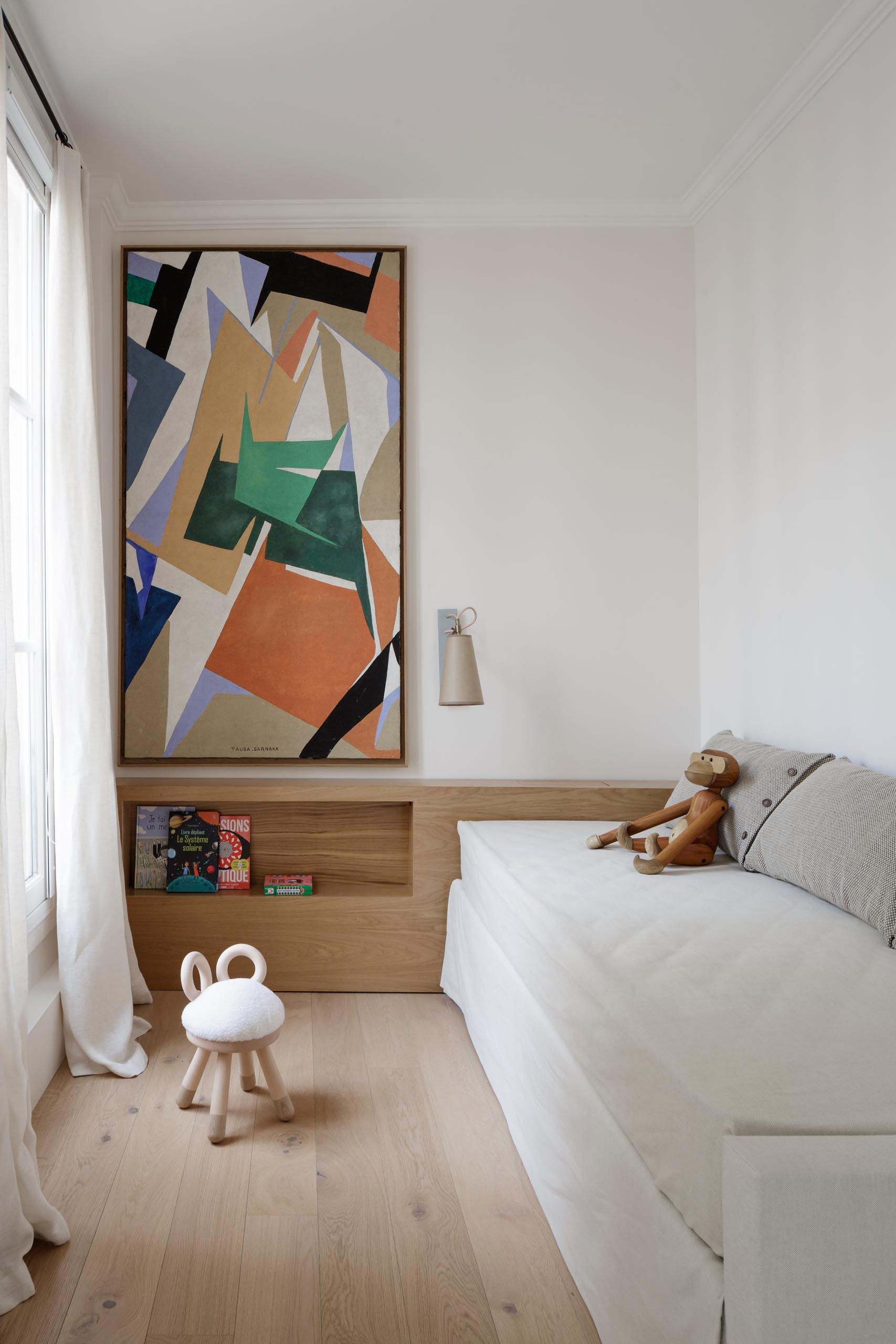 In this modern kids bedroom, calm colors have been paired with textures and artwork to create relaxed and cozy space.