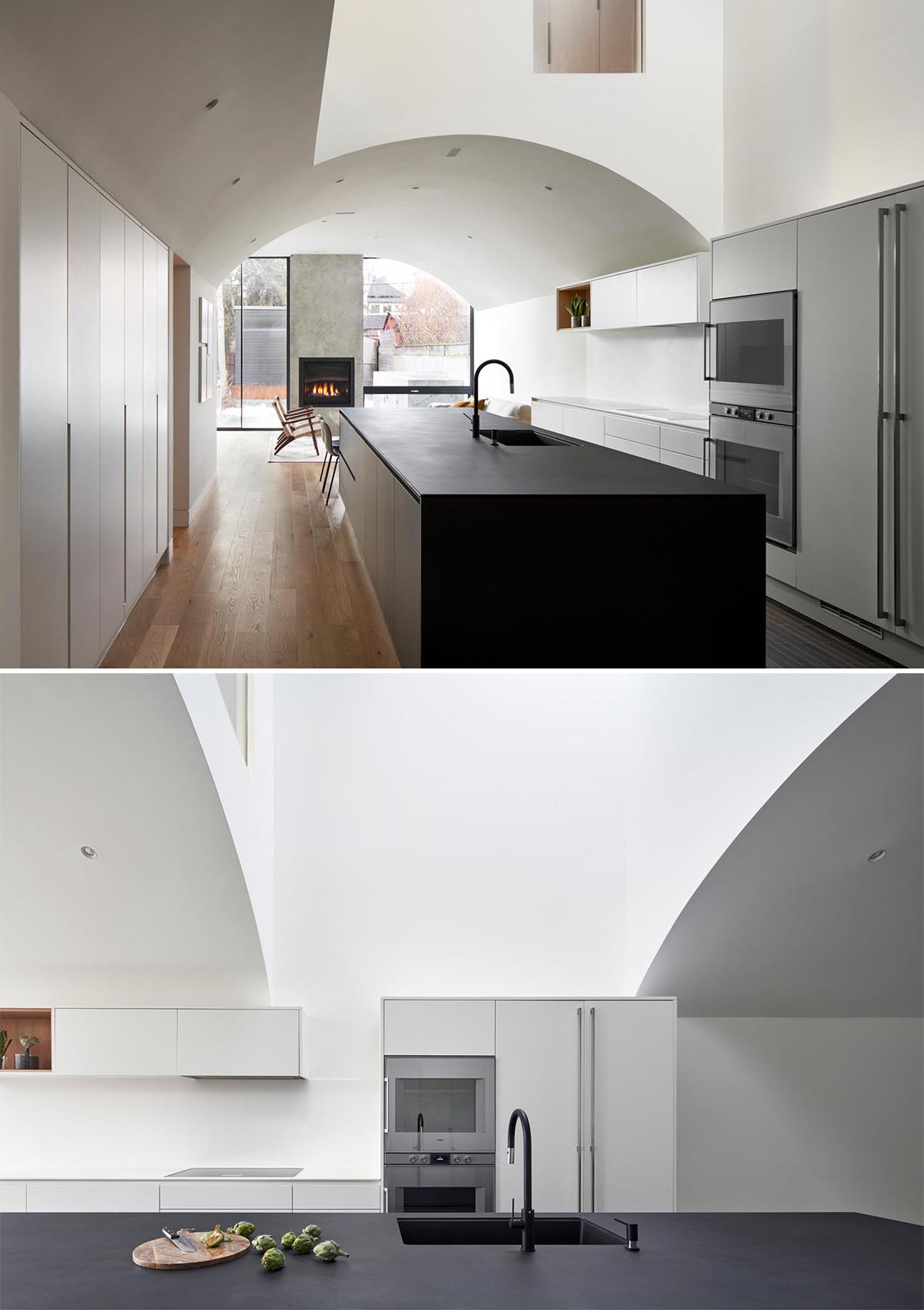 This kitchen, which has white minimalist cabinets that line the wall, and a matte blue kitchen island, also includes a more casual dining area by the living room.