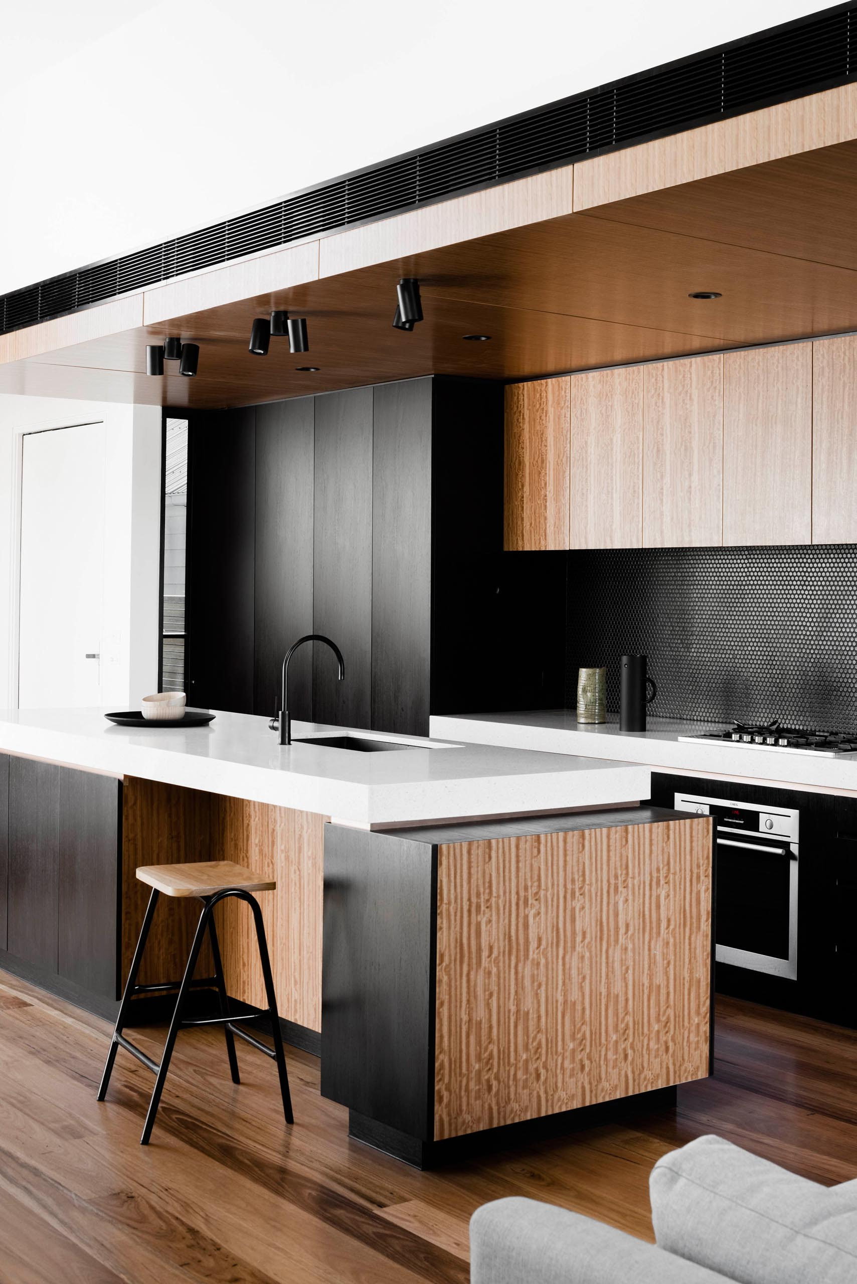 A modern kitchen with black and wood cabinets, a penny tile backsplash, and a white countertop.