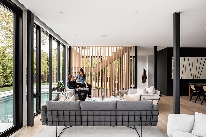 This modern home interior utilizes a simple material palette of blackened steel, light hardwood, and neutral colors, as shown in the open plan main floor of the home.