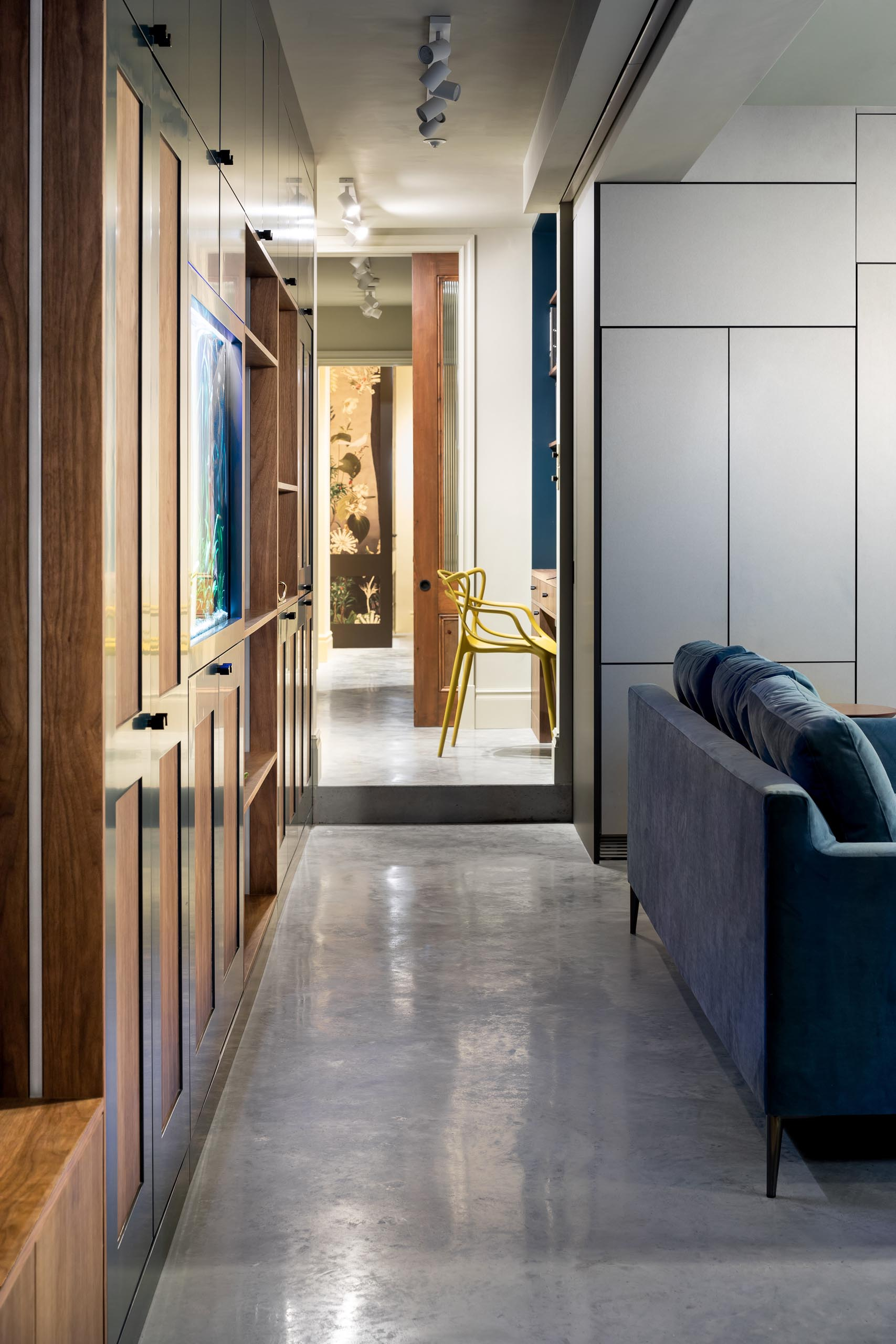 A modern hallway with polished concrete floors and lined with cabinetry and a home office.