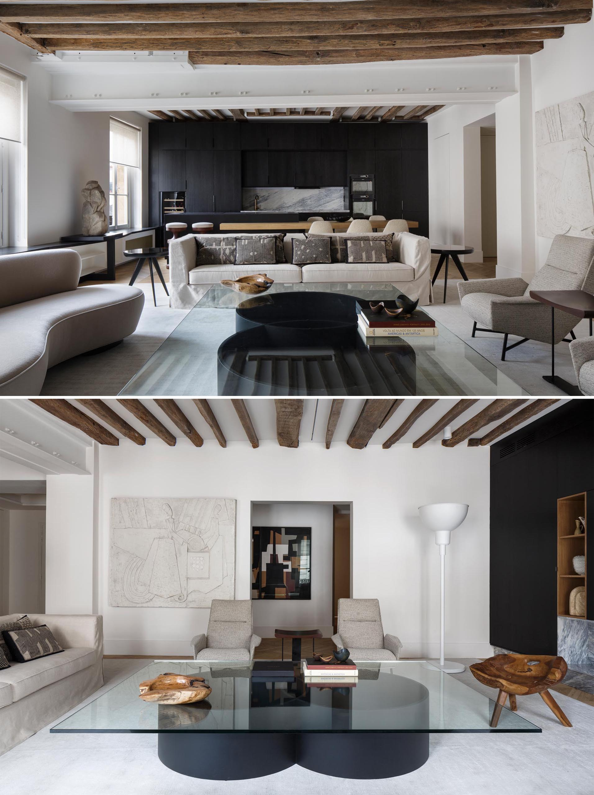 A modern matte black kitchen contrasts the neutral colored living room.