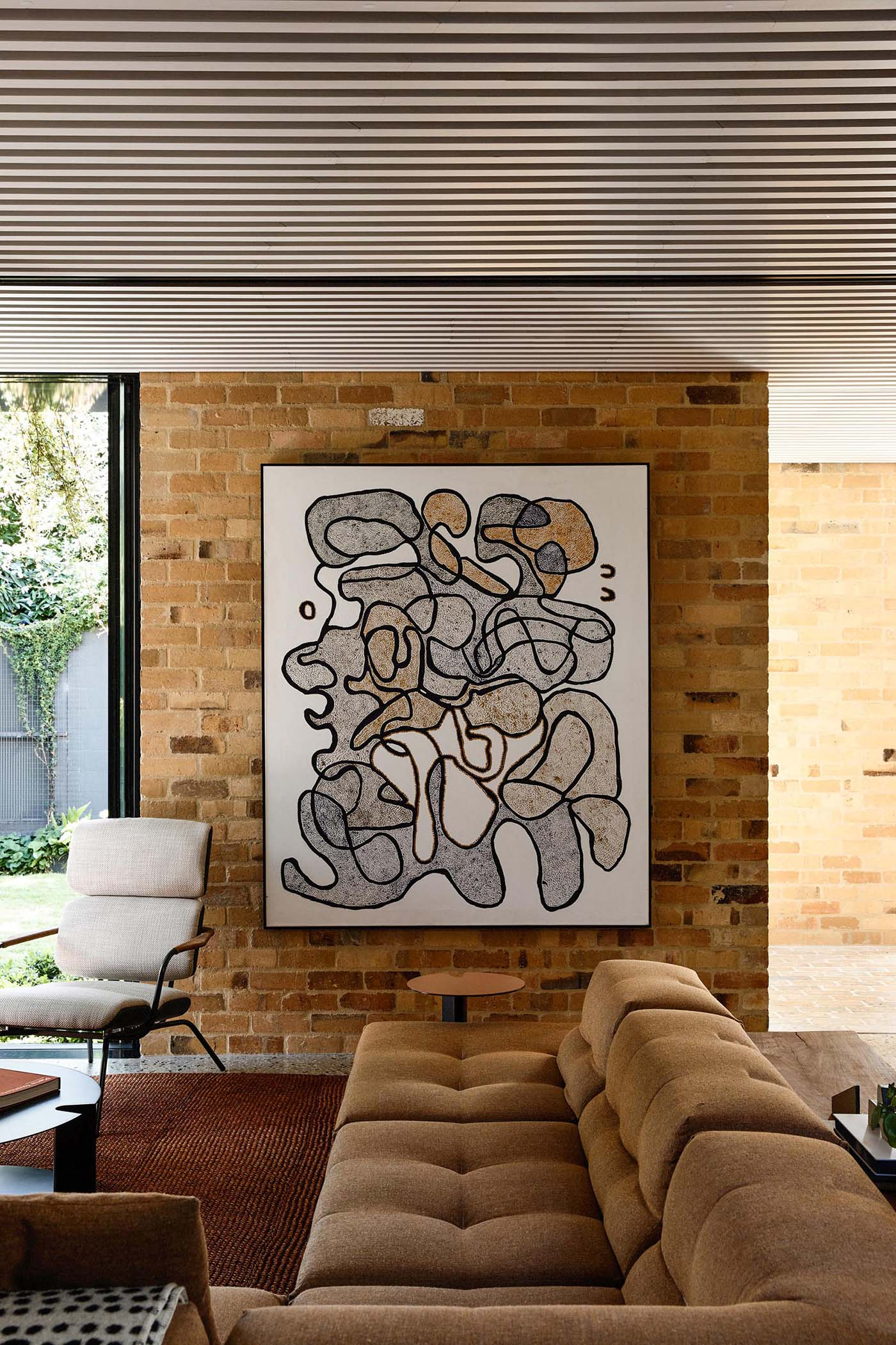 Inside this modern home, the living room is furnished with a large sofa and abstract artwork, while a white slat ceiling adds a unique design element.