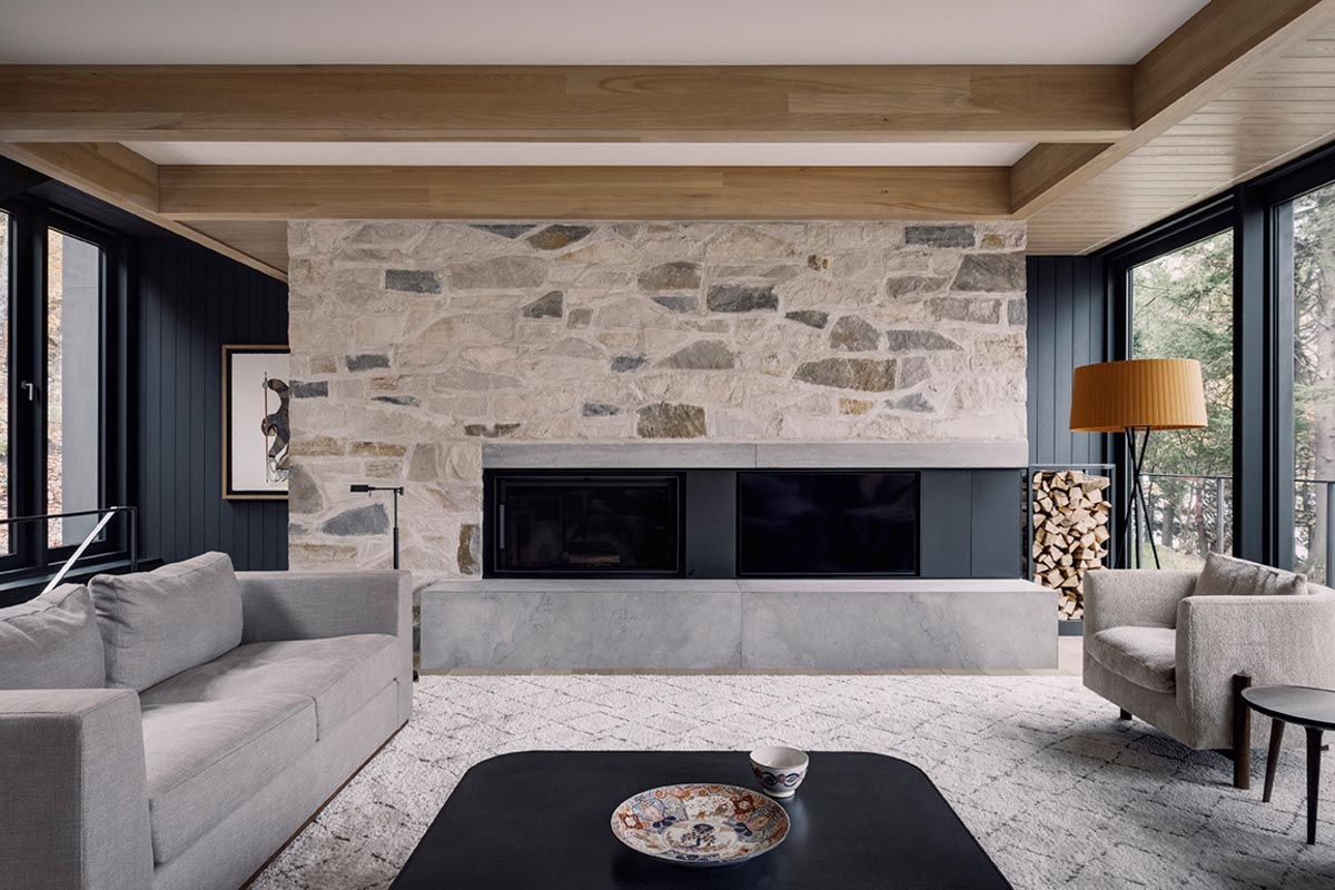 In this modern living room, there's wood accents on the ceiling, while the black fireplace is positioned within a stone wall.