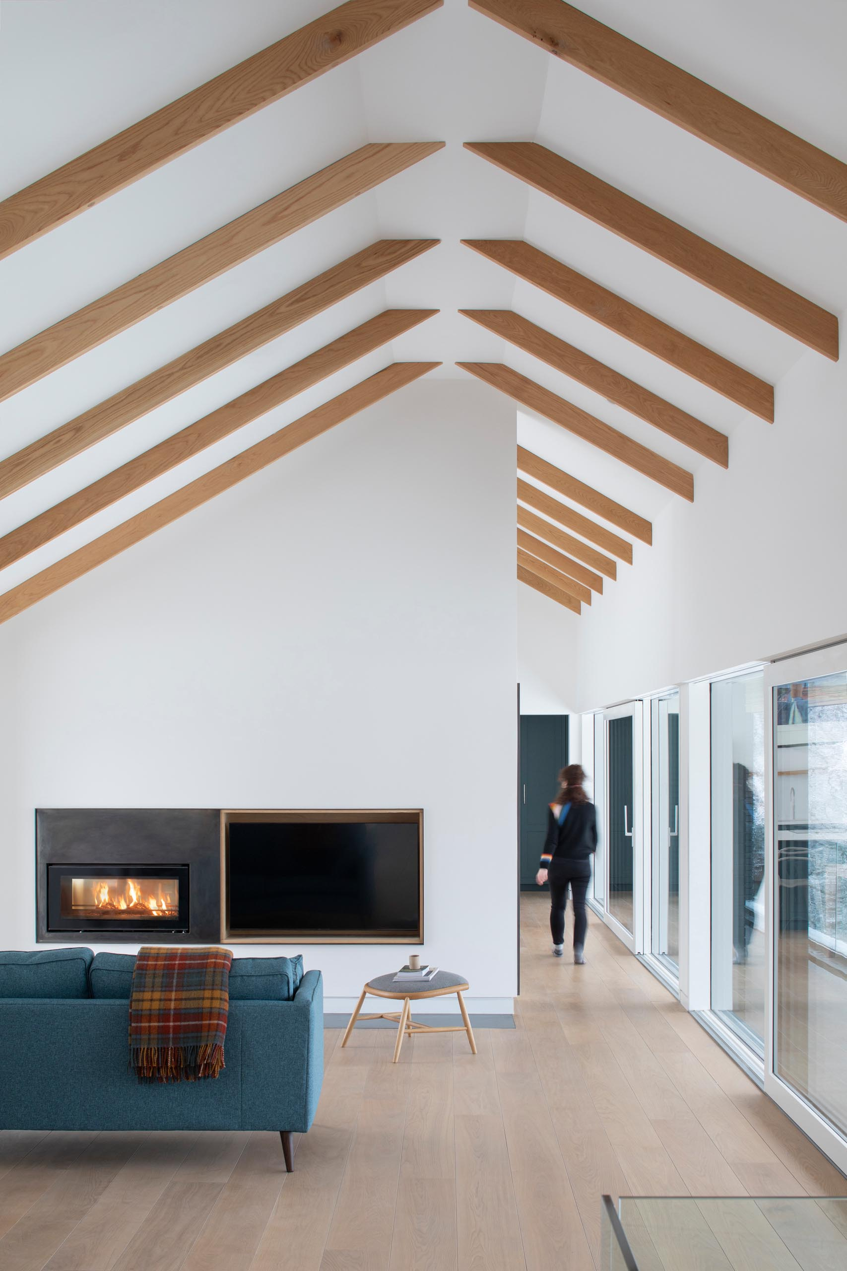 A modern living room with a steel fireplace surround and a wood-lined niche for a television.