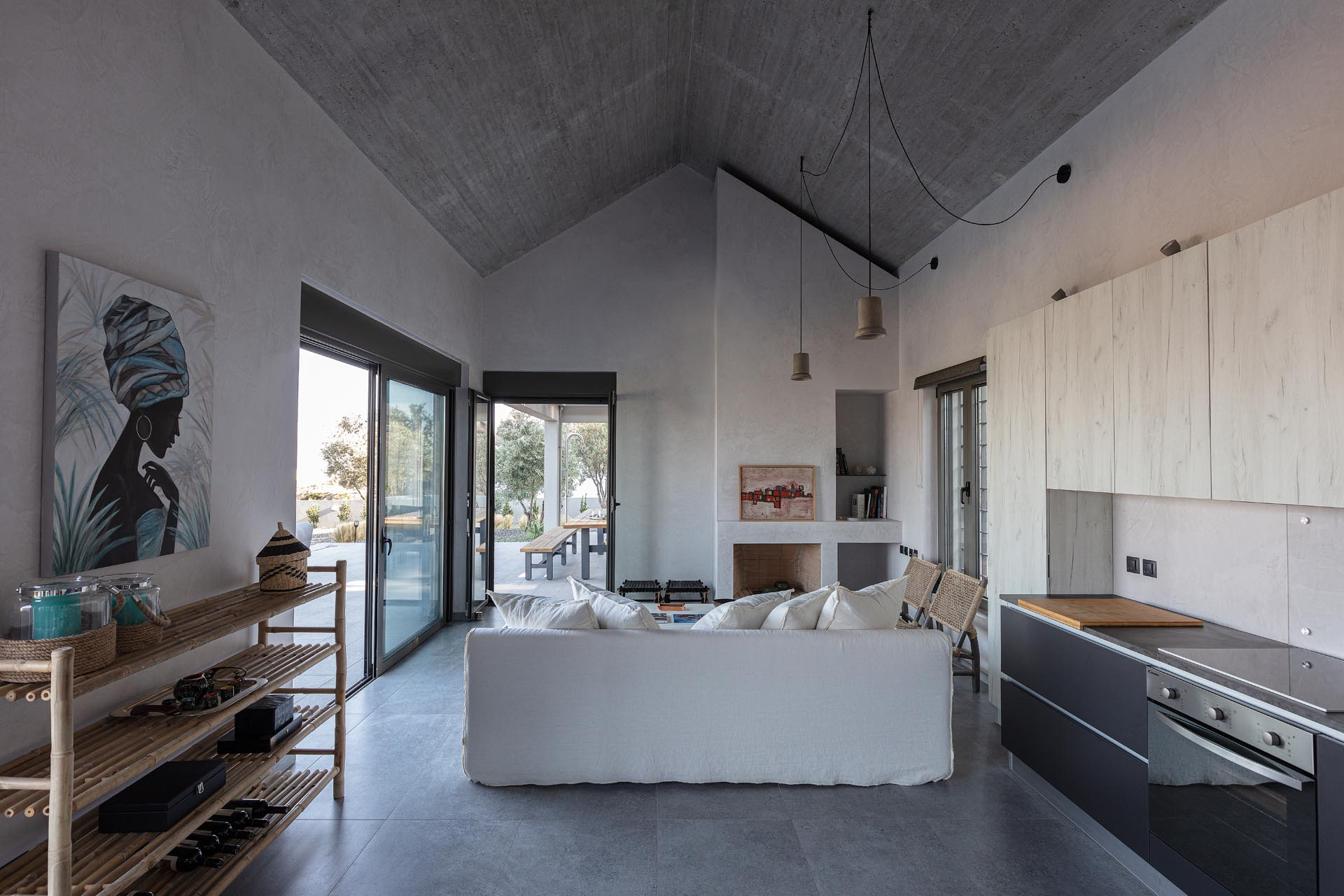 A modern open plan living room and kitchen with a pitched ceiling and doors that open to a terrace.