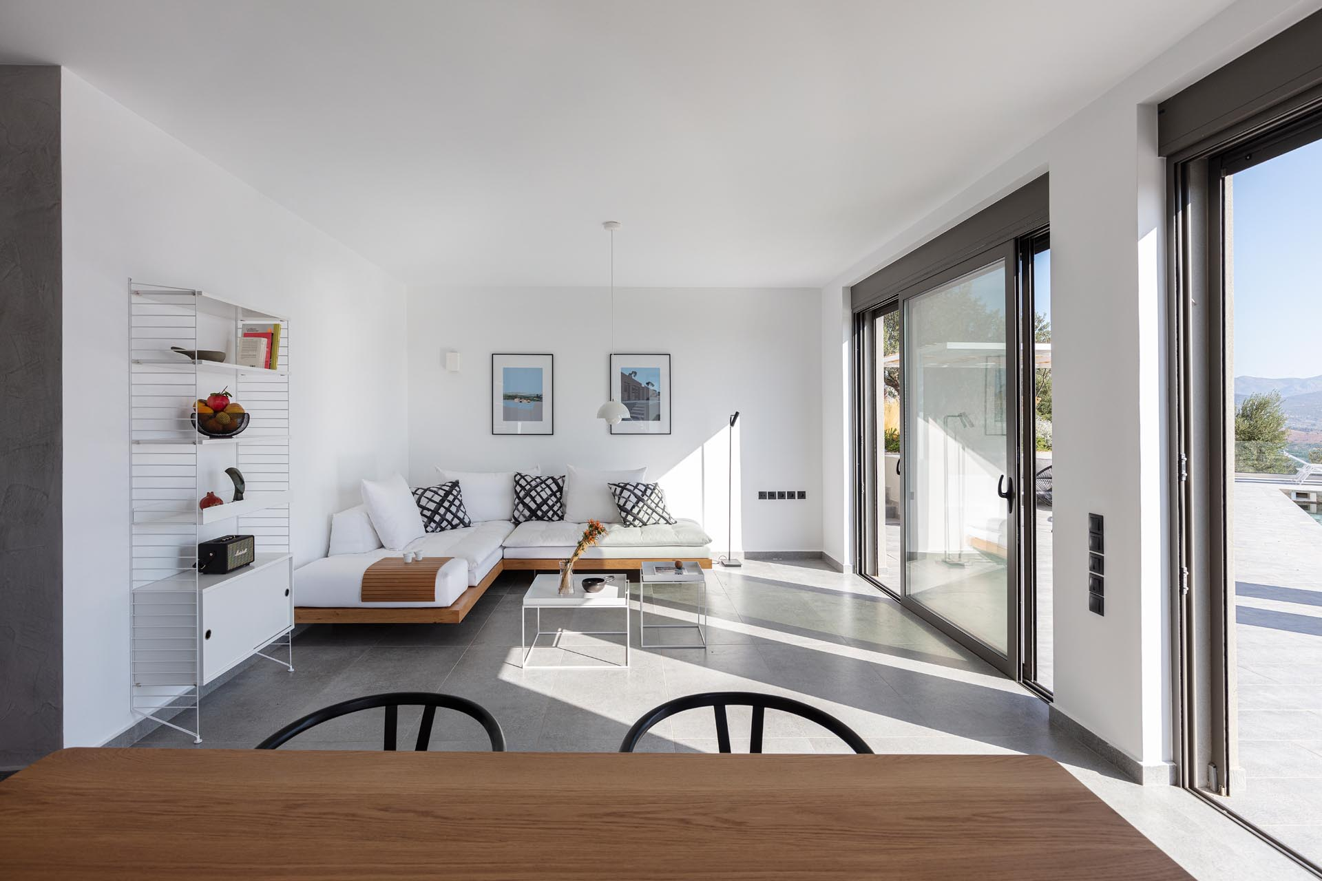 A modern white living room with concrete floors and wood accents.
